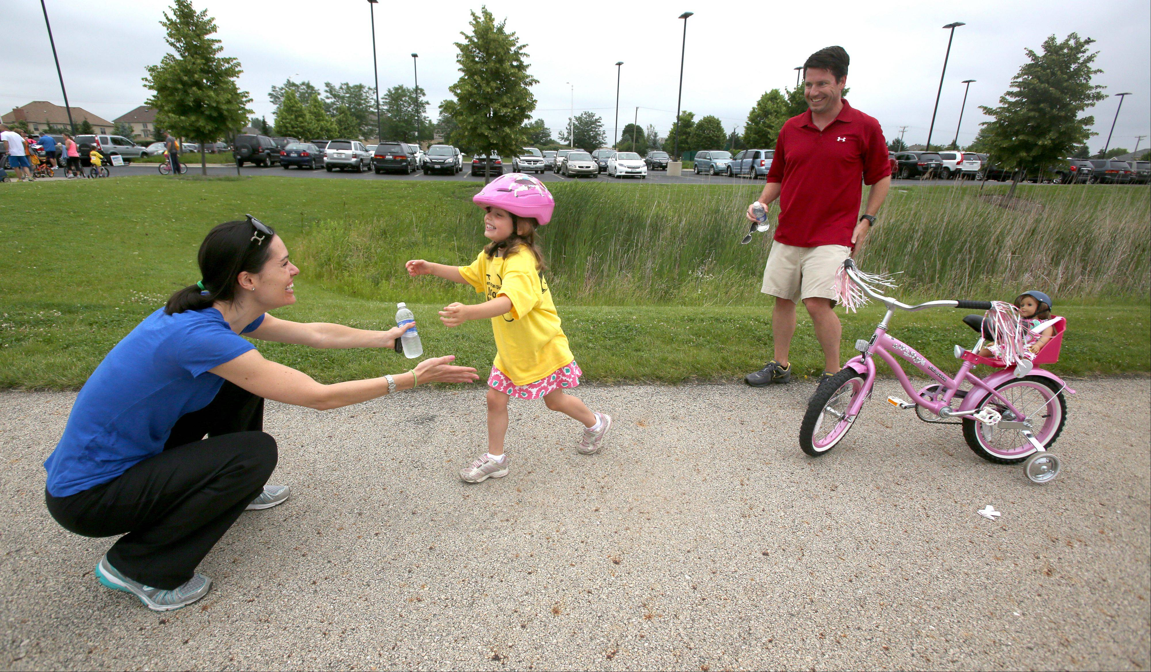 Ava Boren, 2, gets a hug from her mom Robin Boren after finishing the Naperville Park District's first Junior Tour de Naperville, a 1.2 mile bicycle loop held at Commissioner's Park. Alan Boren,
