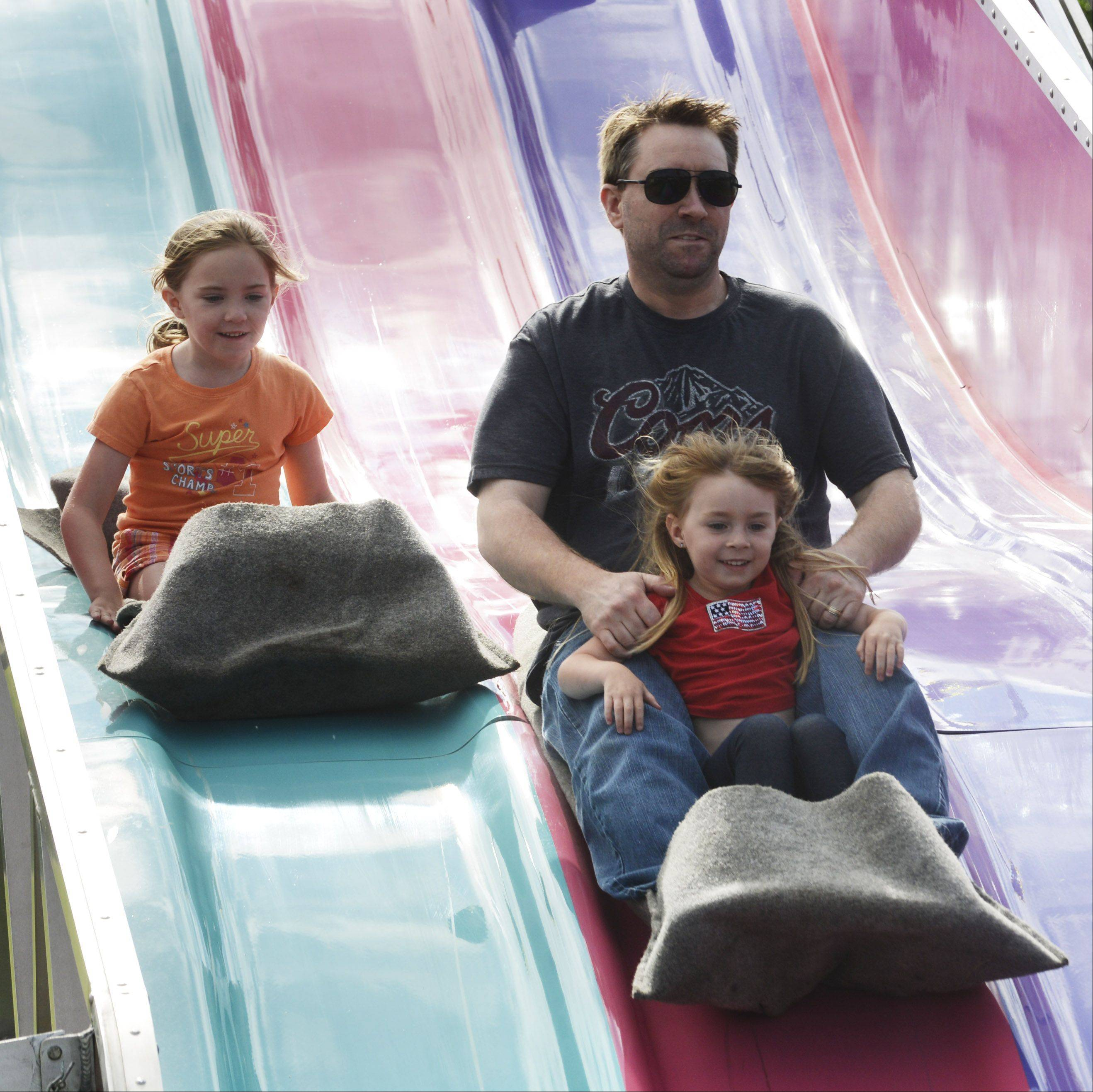 Alex Beagles, of Grayslake, rides the Fun Slide with daughters Sophia, 4, and Gabi, 7, during the Grayslake Family Picnic at Central Park in Grayslake Saturday.