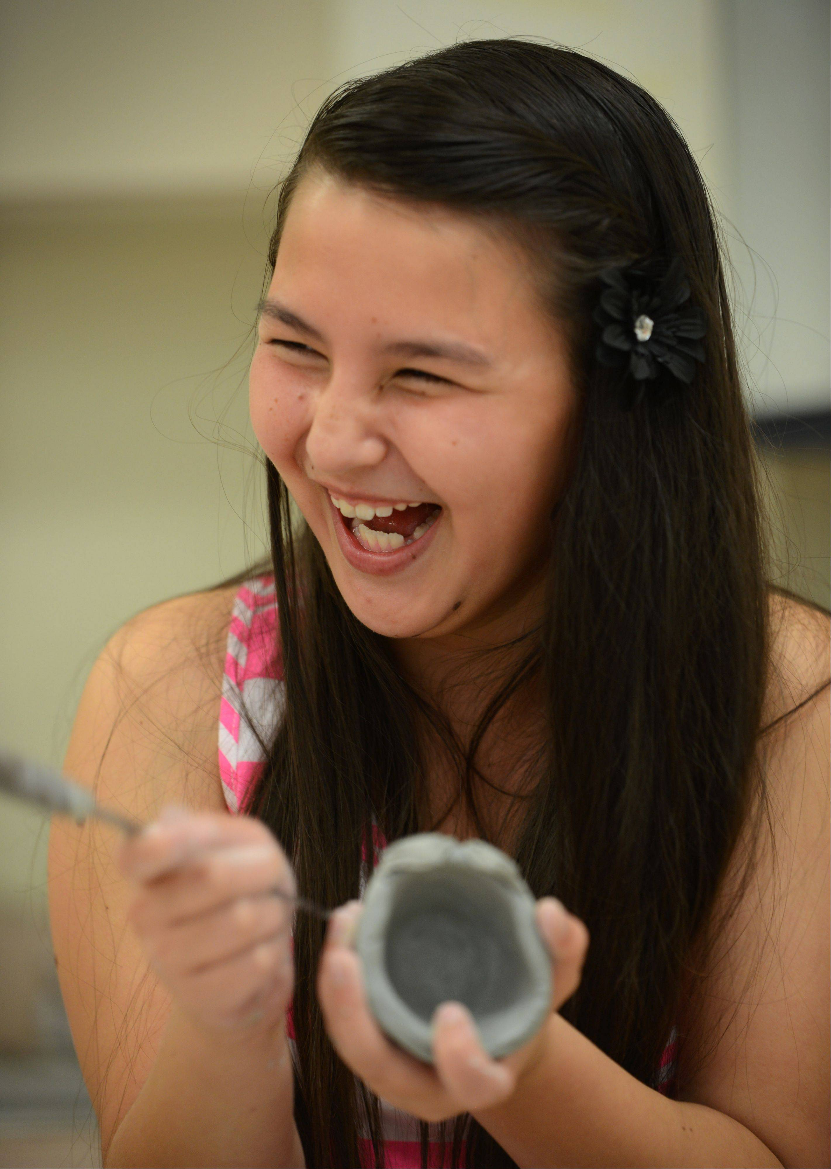 Libertyville School Dist. 70 students are participating in summer school classes at Highland Middle and Rockland Schools through July 11. On Monday, fifth-grade-student Amber Tse has fun with friends while working on a ceramics project.