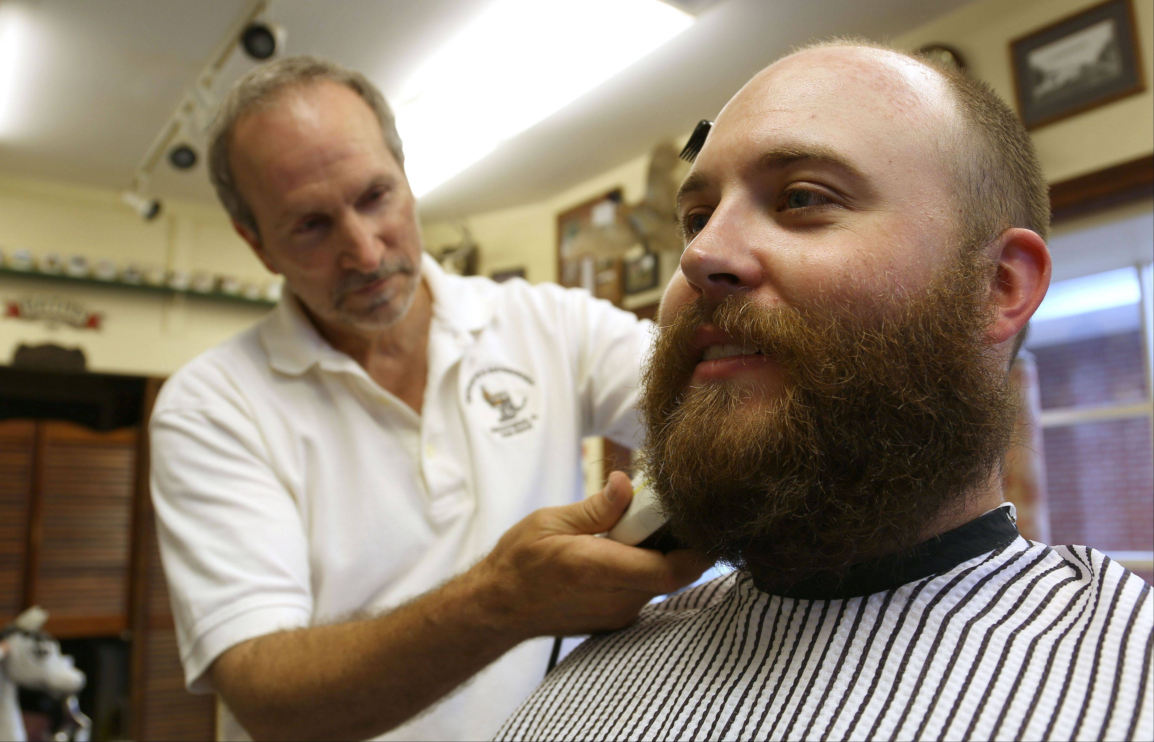 Patrick Ringel gets his playoff beard shaved at Tremonte's Barbershop in Wauconda Tuesday. For a donation of $10 people received a shave, a free 10oz. reusable stadium cup donated by Bulldogs Grill, and a complimentary ticket for a drink from Middleton's. A portion of the proceeds will be donated to the Wauconda Park District Youth Sports Program.