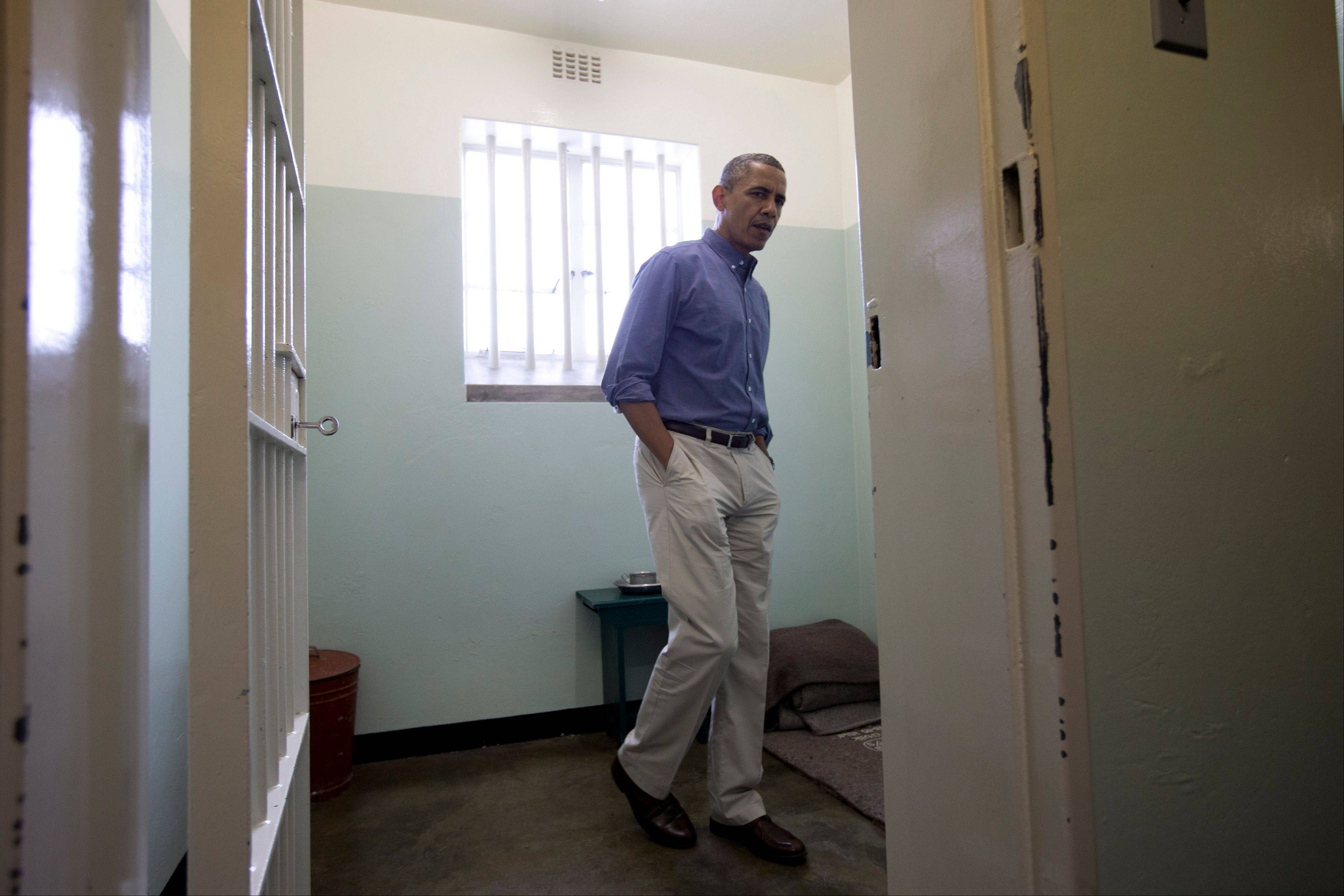 President Barack Obama looks out from Section B, prison cell No. 5, on Robben Island, South Africa, on Sunday. This was former South African president Nelson Mandela's cell, where spent 18-years of his 27-year prison term on the island locked up by the former apartheid government.