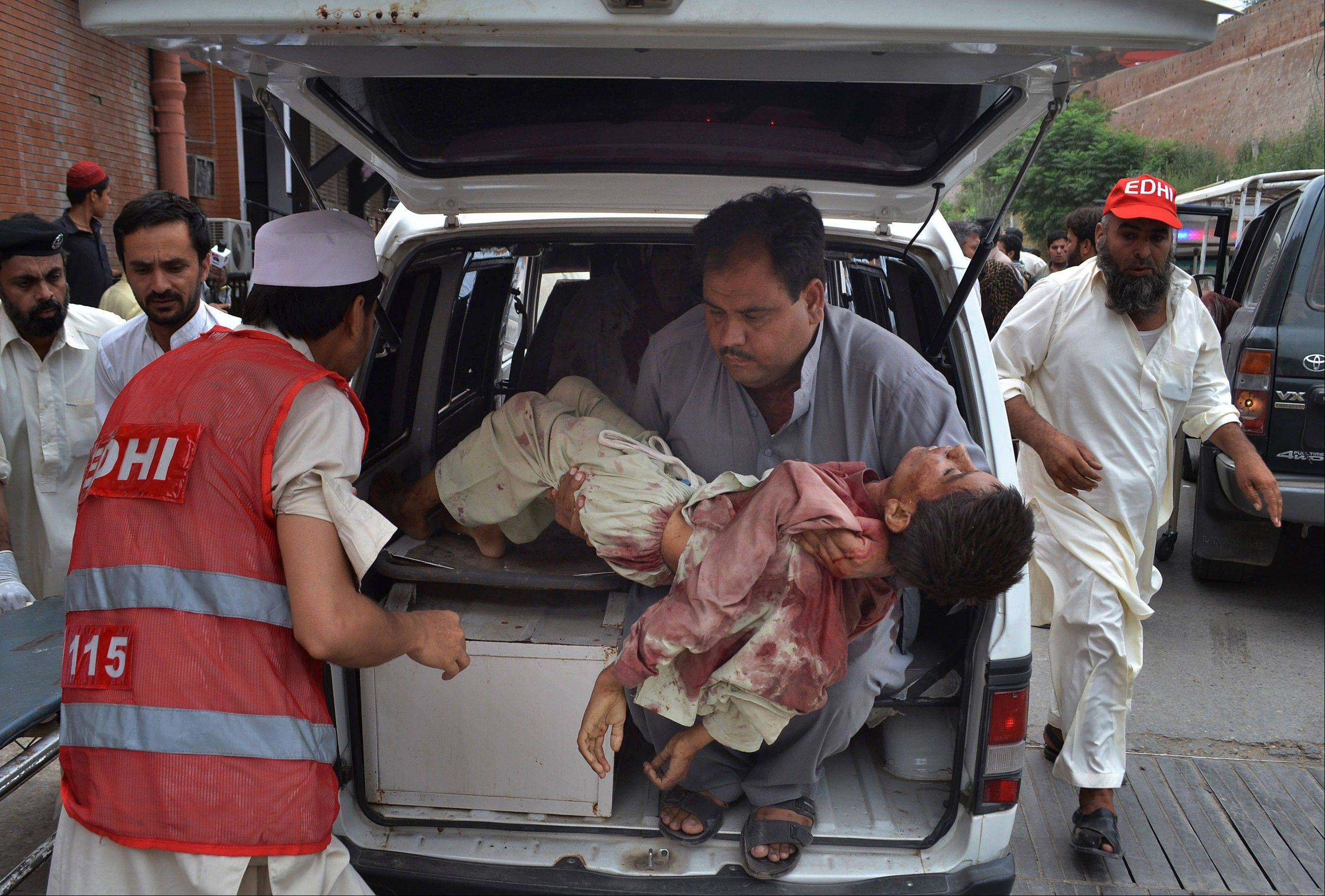 A Pakistani man carries a critically injured boy, a victim of a Sunday car bombing, from an ambulance upon his arrival at a hospital in Peshawar, Pakistan.