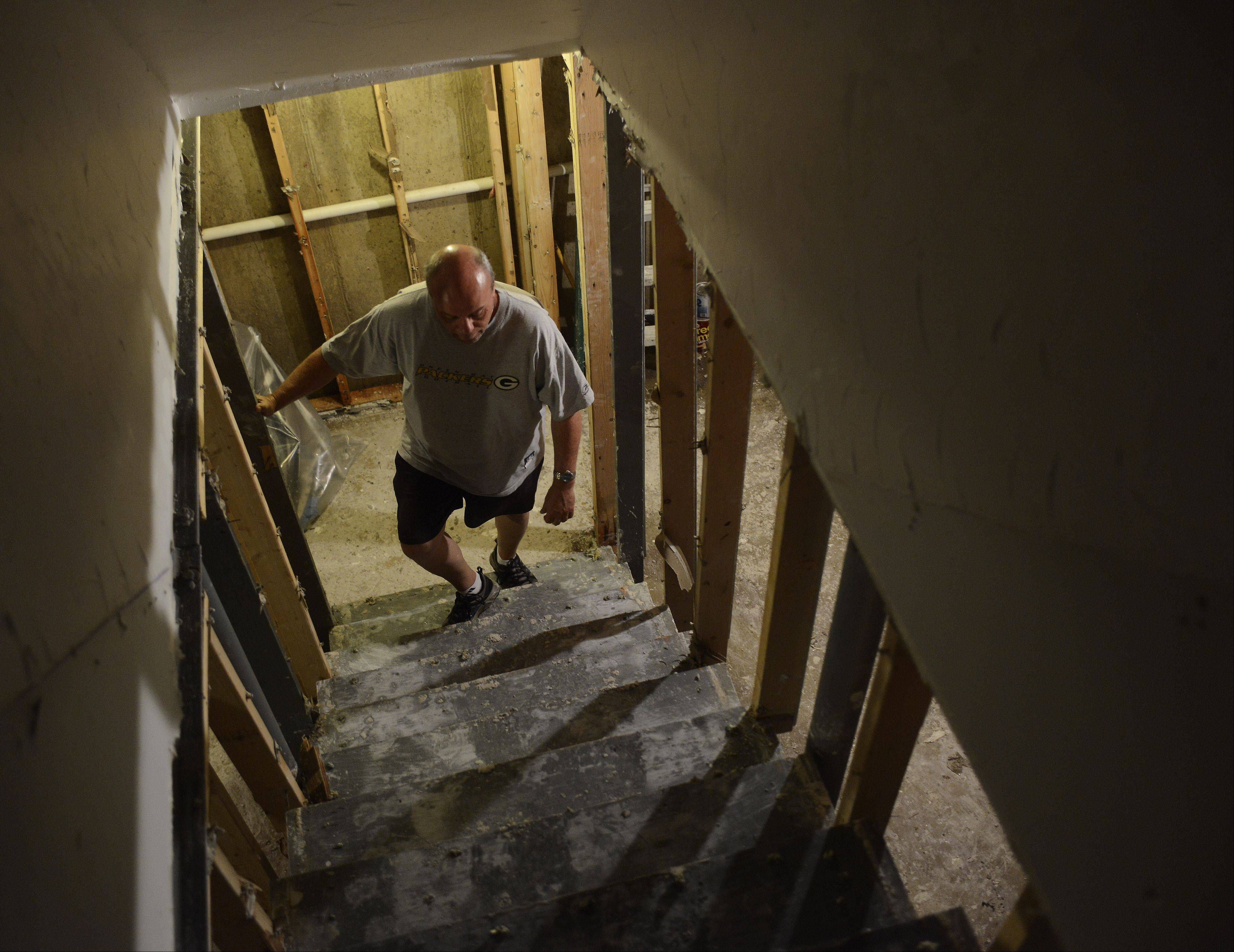 Dan Donatell climbs the stairs of his Lake Zurich home on Bristol Trail Road Saturday after flooding from Wednesday's storm destroyed his appliances and forced the removal of everything in his finished basement down to the studs.