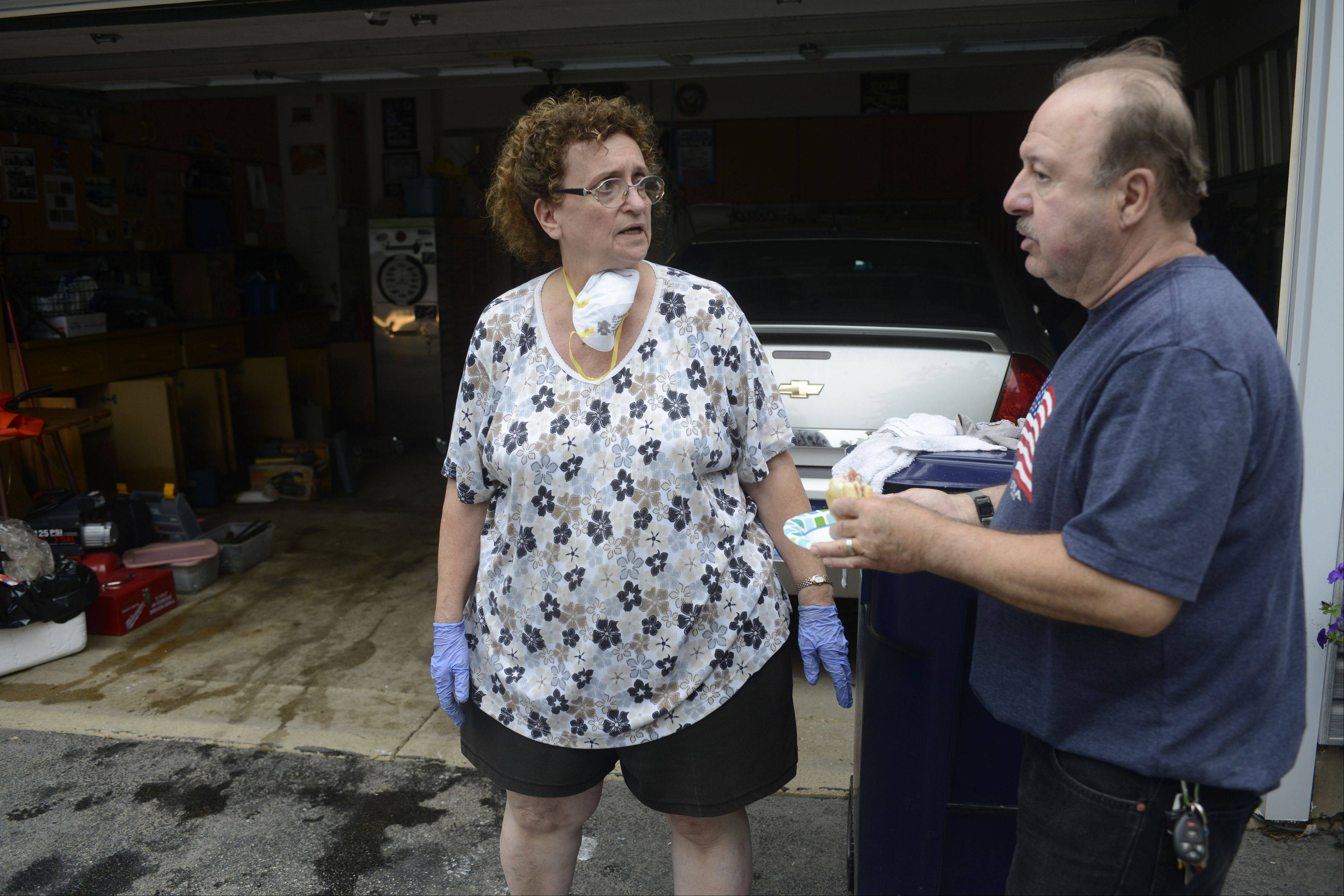 Rosemary Sebastian talks with her husband Ed Saturday as cleanup from Wednesday's storm continues at their Lake Zurich home.