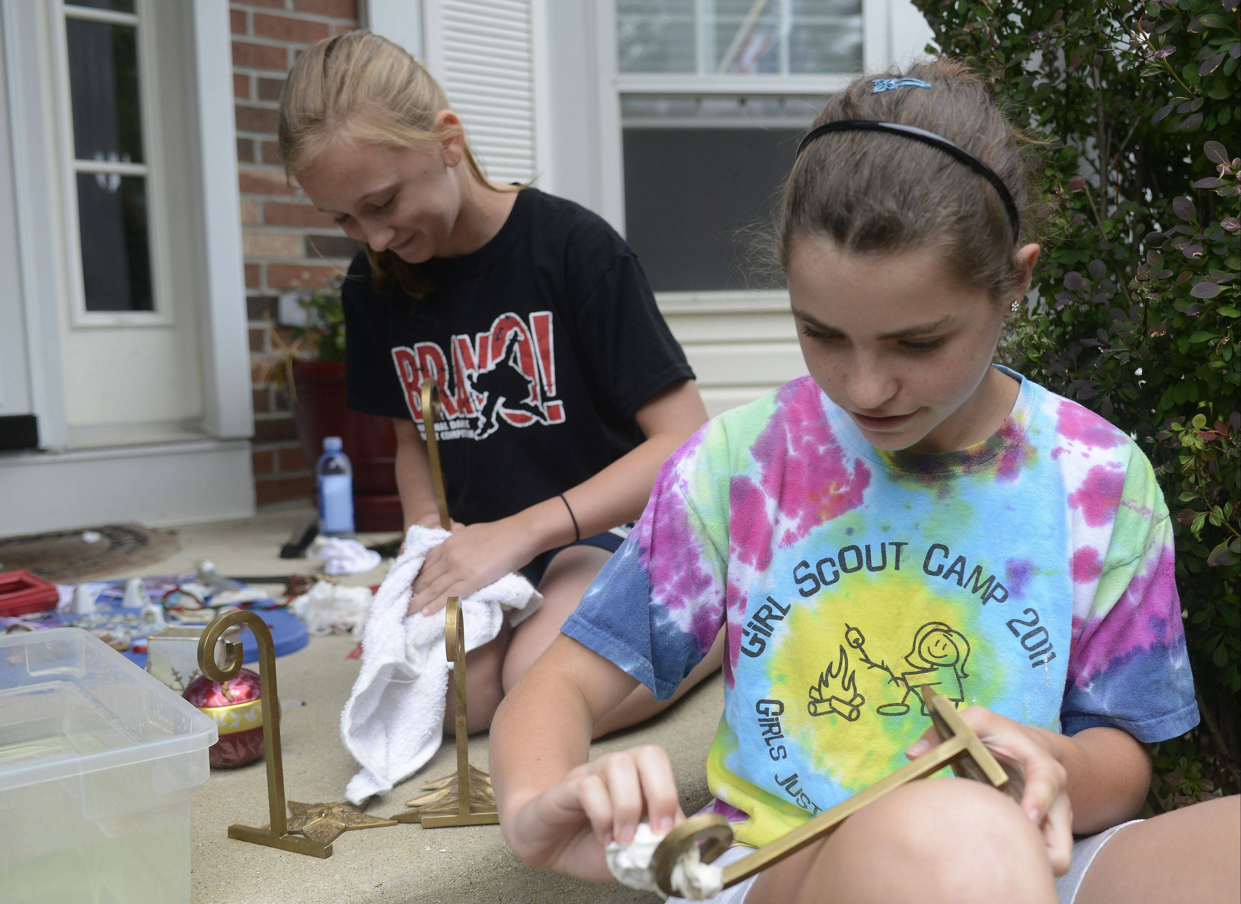 Volunteers Kelly Brenner, left, and Emma Belew, both 12-year-olds from Lake Zurich, help a Stanton Court family Saturday by cleaning small items affected by Wednesday's flooding.