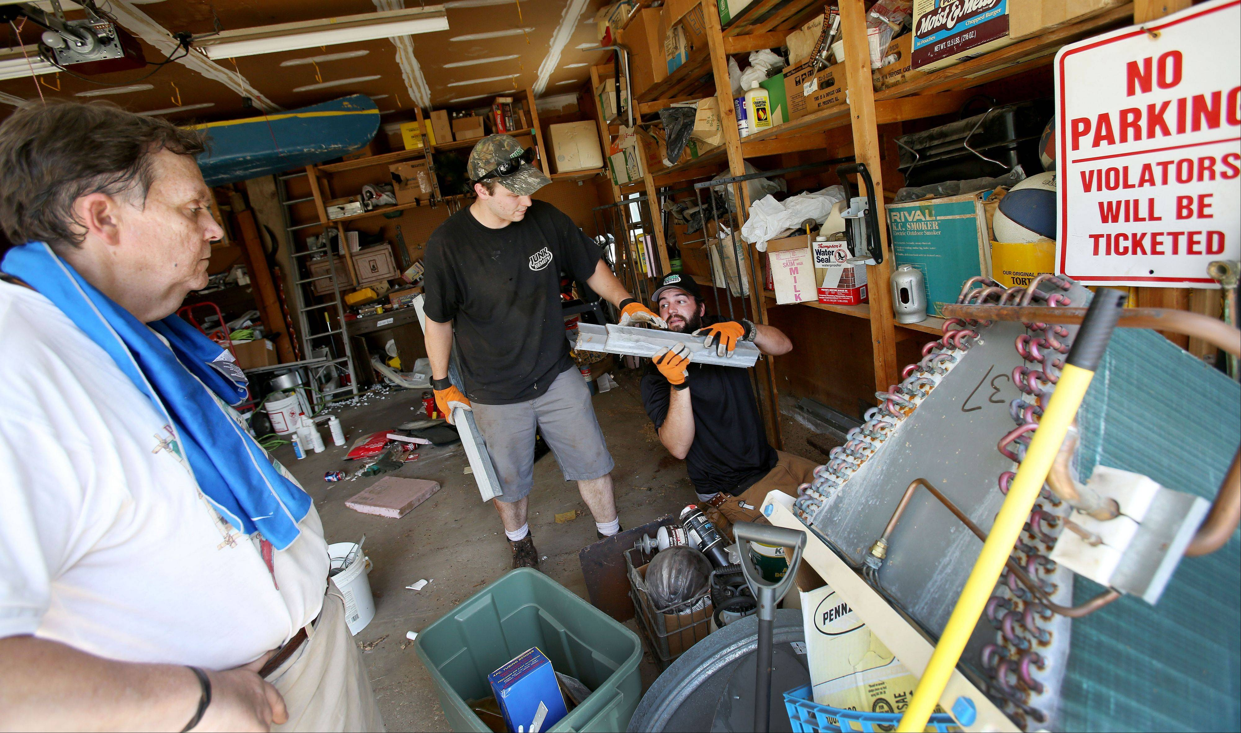 Keeping a watchful eye on the process, Bob DeBellis makes peace with the removal of his items from his garage in Roselle. Junk Remedy co-owner Nick De Giulio, kneeling, hands items to team member Derek Moser as part of the garage makeover.