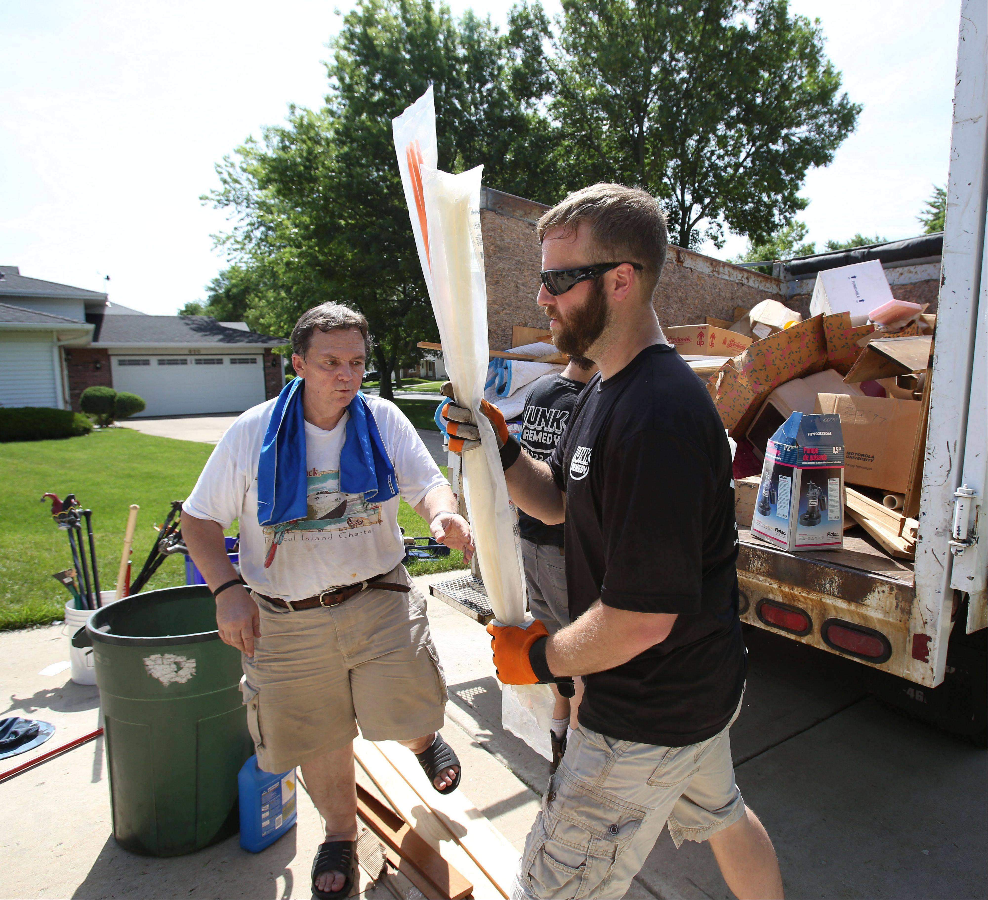 Exercising his veto rights, garage owner Bob DeBellis has Junk Remedy's Adam Brehmer, right, return an item DeBellis isn't ready to see go from his once-cramped garage.