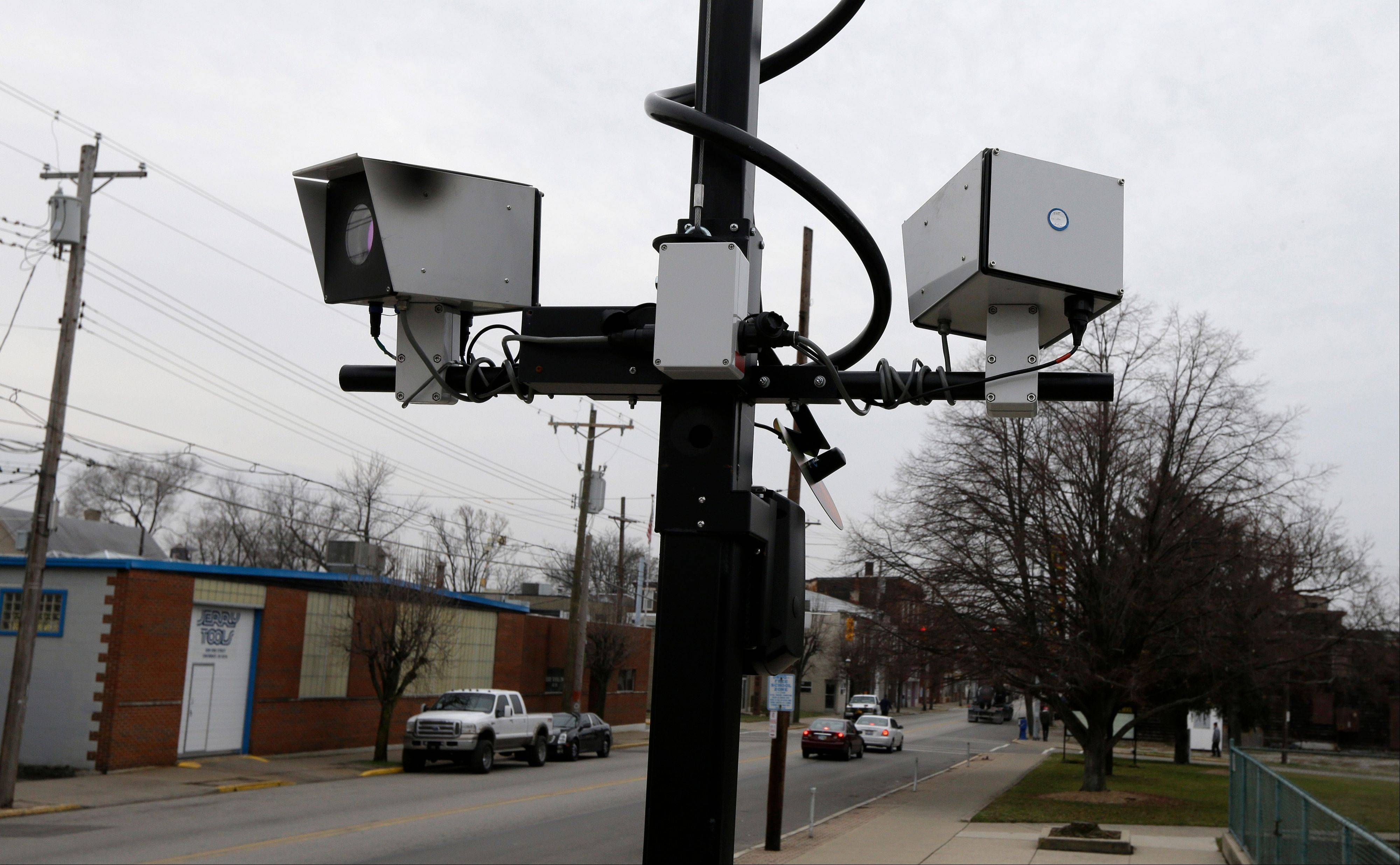 A pair of traffic cameras on Vine Street in Elmwood Place, Ohio. The village was on pace to assess $2 million in traffic fines in six months until a lawsuit brought a ruling from a judge forcing the village to stop using the cameras. The village is appealing the ruling.
