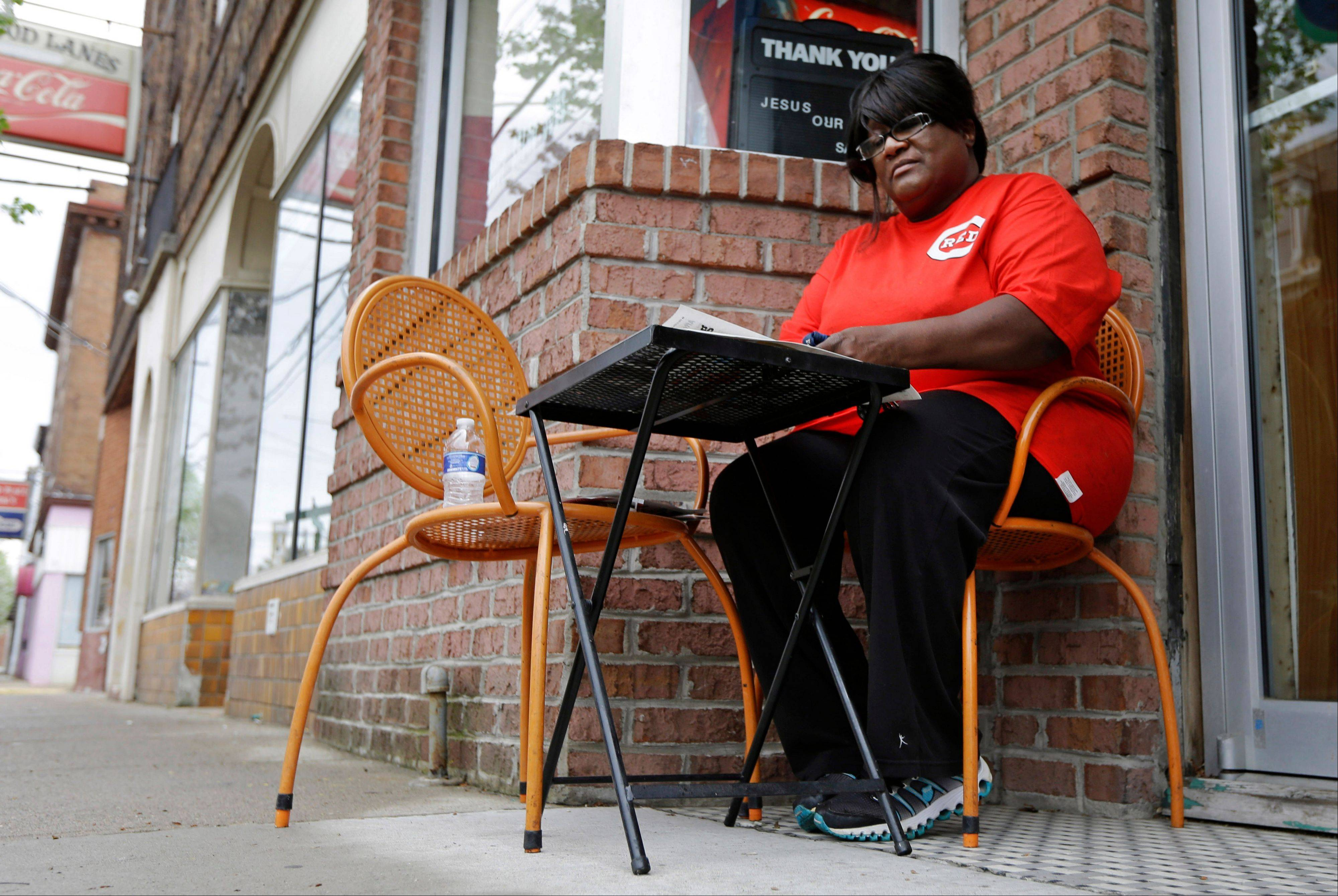 Catherine Jones sits outside her namesake restaurant, in Elmwood Place, Ohio. Jones understands the community's need to install speed cameras to quell speeding, but now she is among many small business owners worried that the cameras have given the village a speed trap stigma.