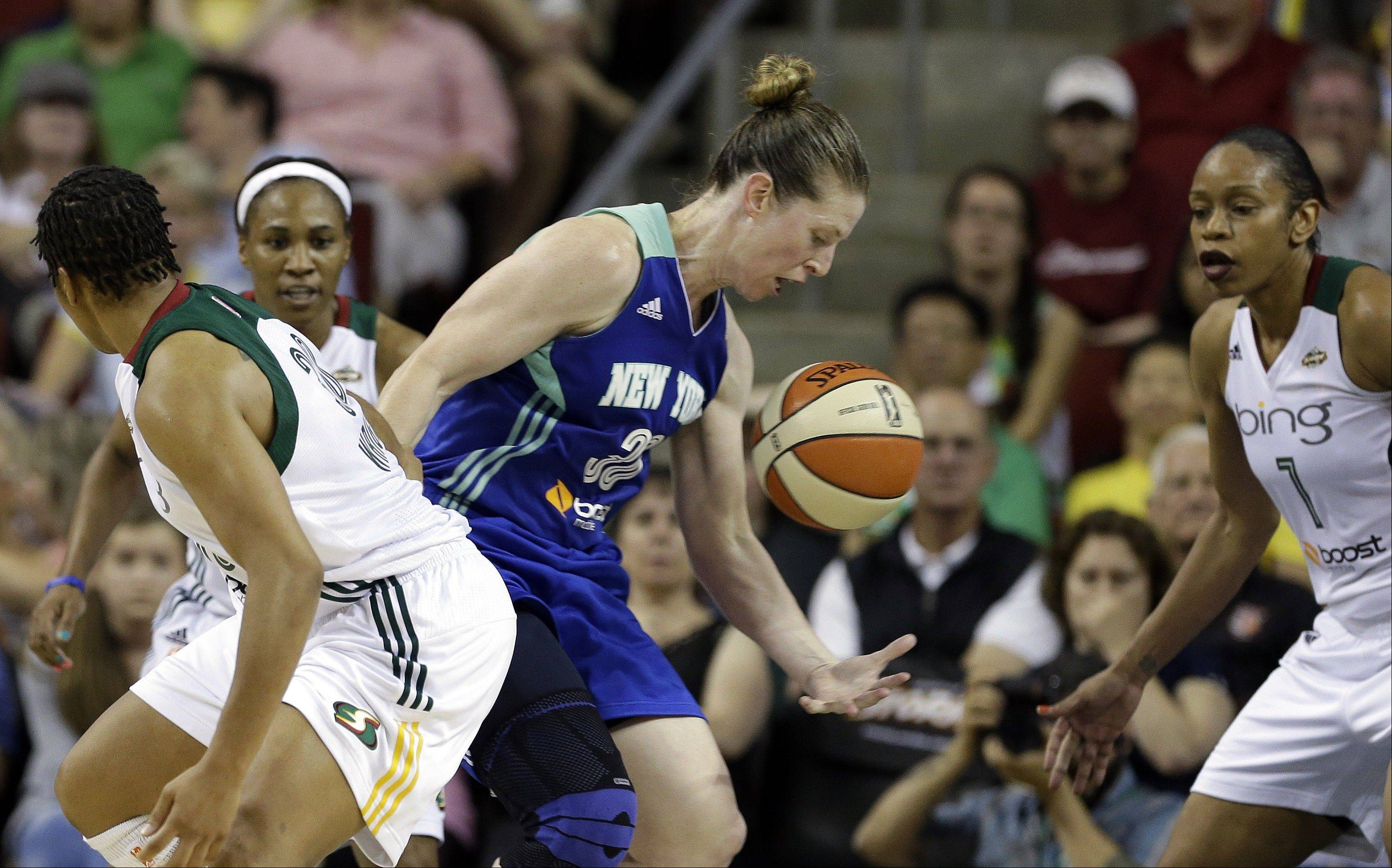 New York Liberty's Katie Smith, center, tries to hold on to the ball between Seattle Storm's Tina Thompson, right, Tanisha Wright, left, and Temeka Johnson in the second half of a WNBA basketball game Friday, June 28, 2013, in Seattle. New York won 67-62.