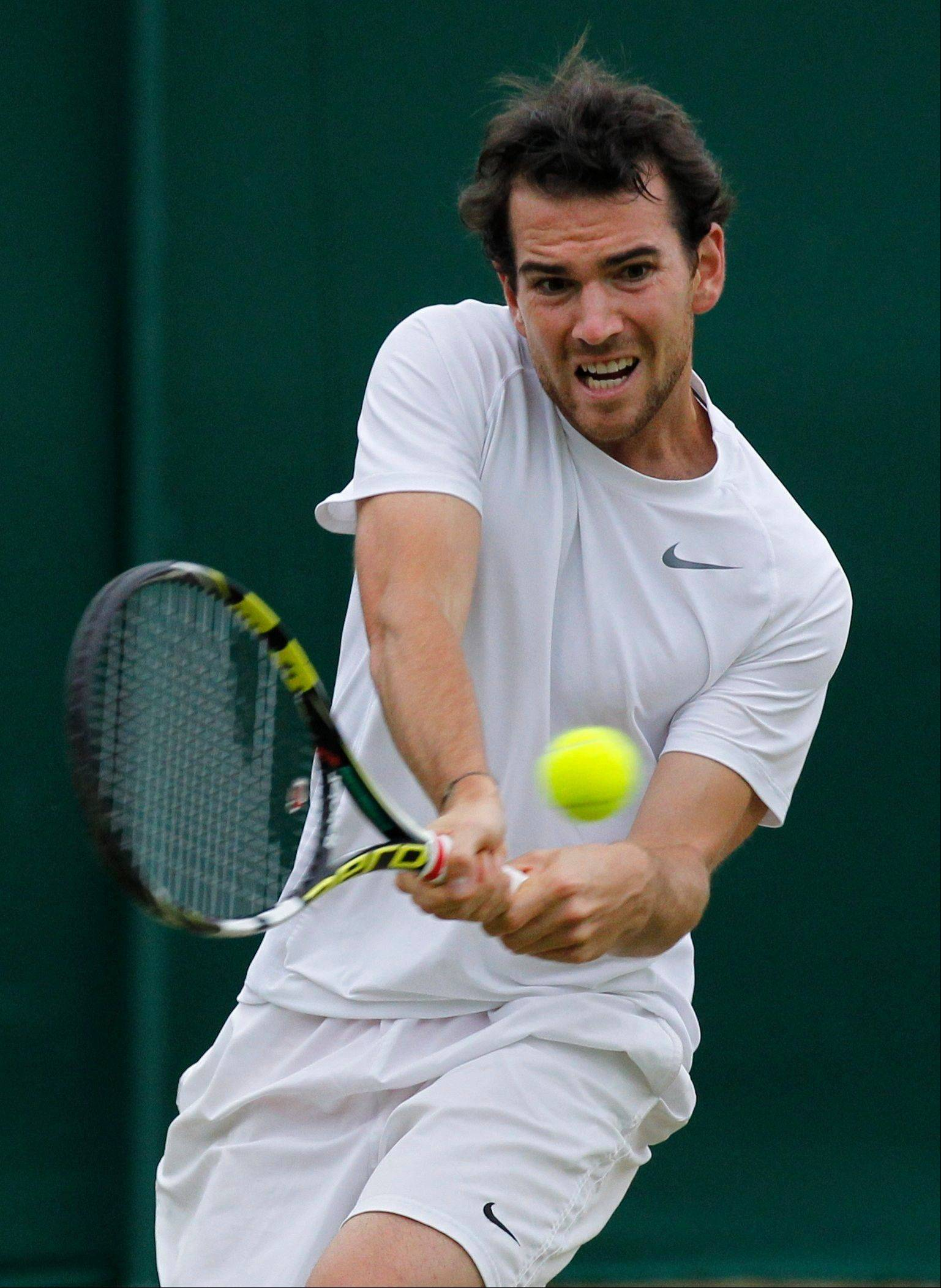 Adrian Mannarino of France plays a return to Dustin Brown of Germany during their men's singles match Friday at in Wimbledon.