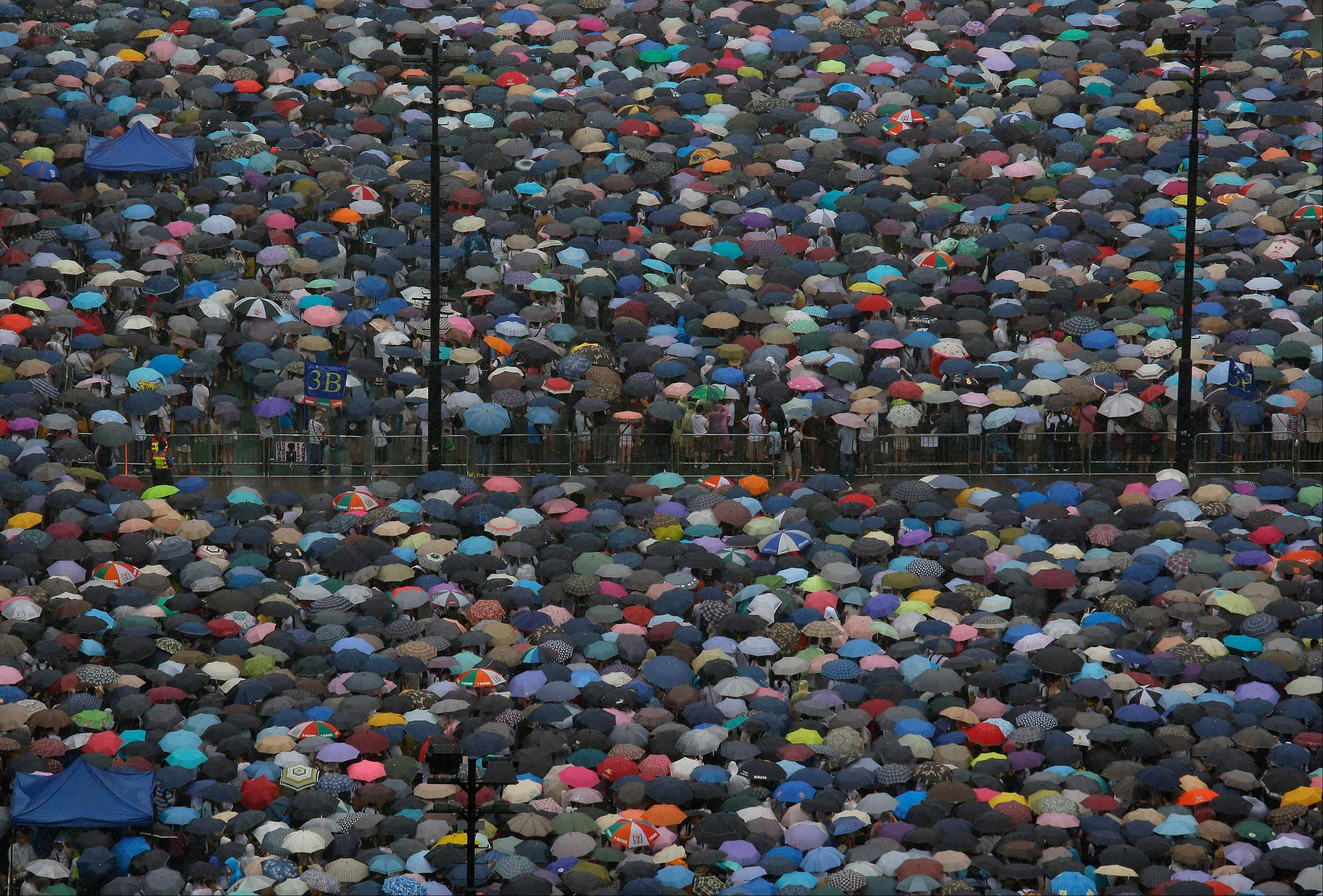 Tens of thousands of Hong Kong residents gather at Victoria Park before an annual pro-democracy protest in Hong Kong Monday. The protesters demanded their widely disliked Beijing-backed leader resign and pressing for promised democratic reforms so they can choose their own top representative.