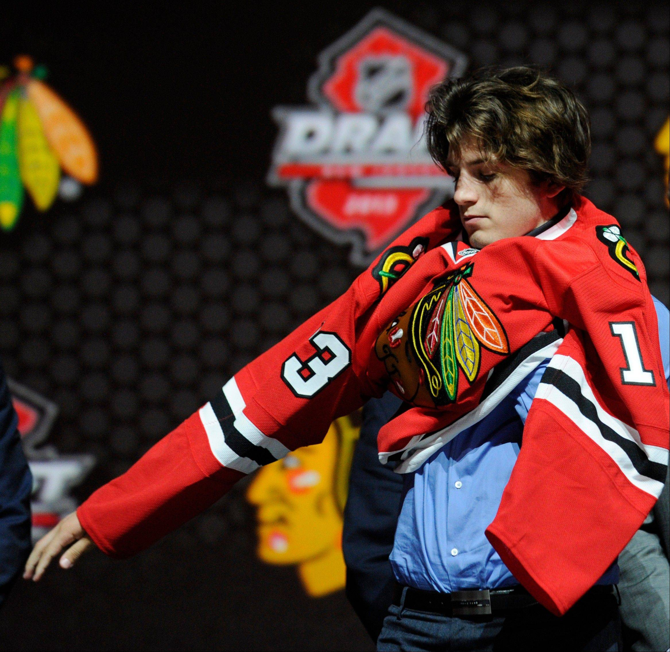 Ryan Hartman, a winger and native of West Dundee, pulls on a Chicago Blackhawks sweater after being chosen 30th overall in the first round of the NHL hockey draft Sunday in Newark, N.J.
