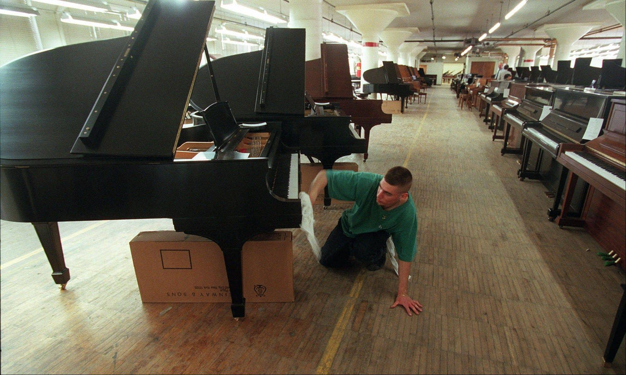 A worker applies the finishing touches to a Steinway piano at piano maker's factory in the Queens Borough of New York. The famed piano maker Steinway is being acquired by private equity firm Kohlberg & Co. for about $438 million.