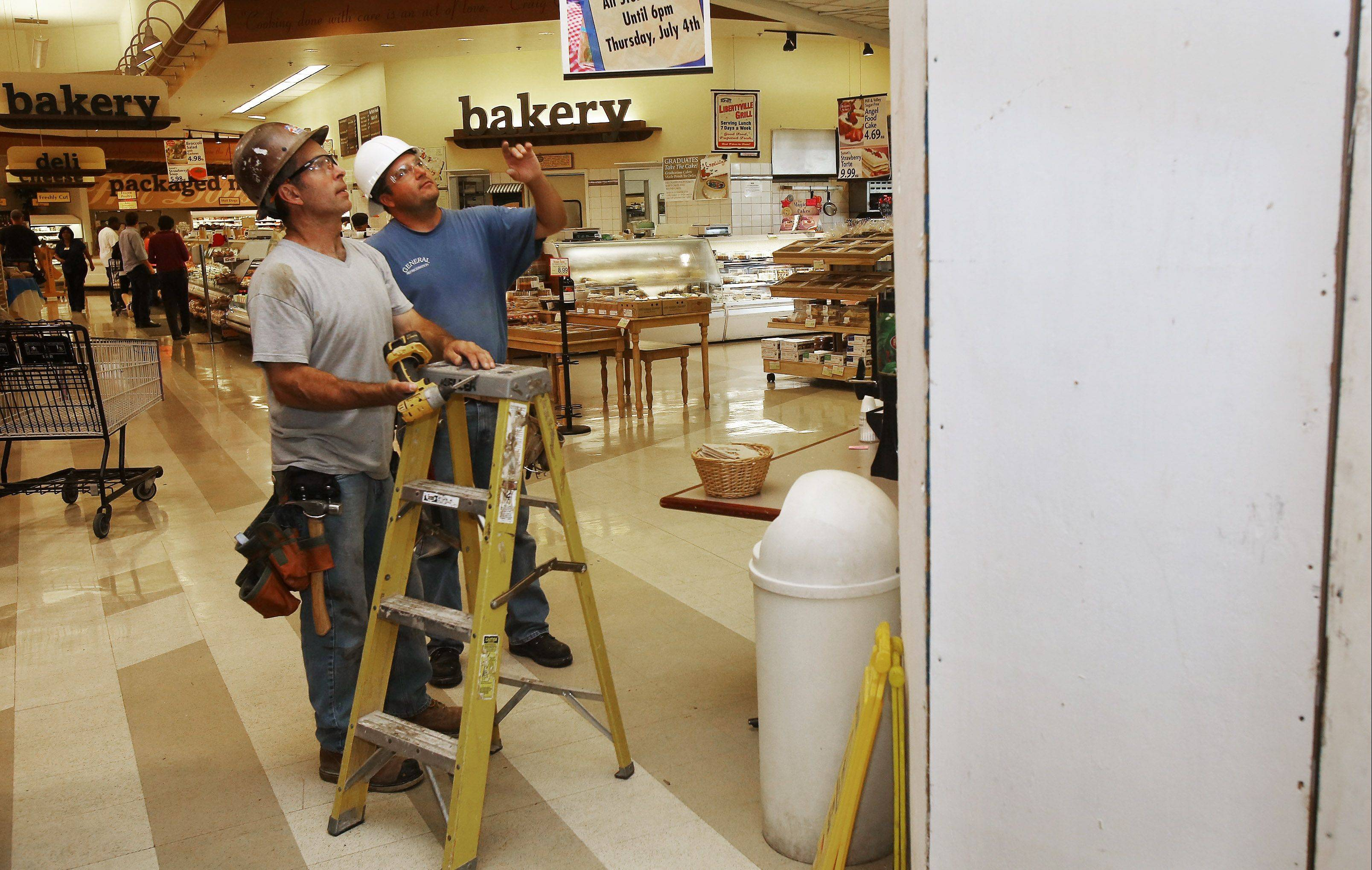 Carpenters John Bazan, left, and Brian Uteg of Novak Construction discuss the new bar for craft beers at Sunset Foods in Libertyville. Sunset is undergoing renovation to provide a variety of improvements, including a full-service floral design center and an outdoor cafe area.