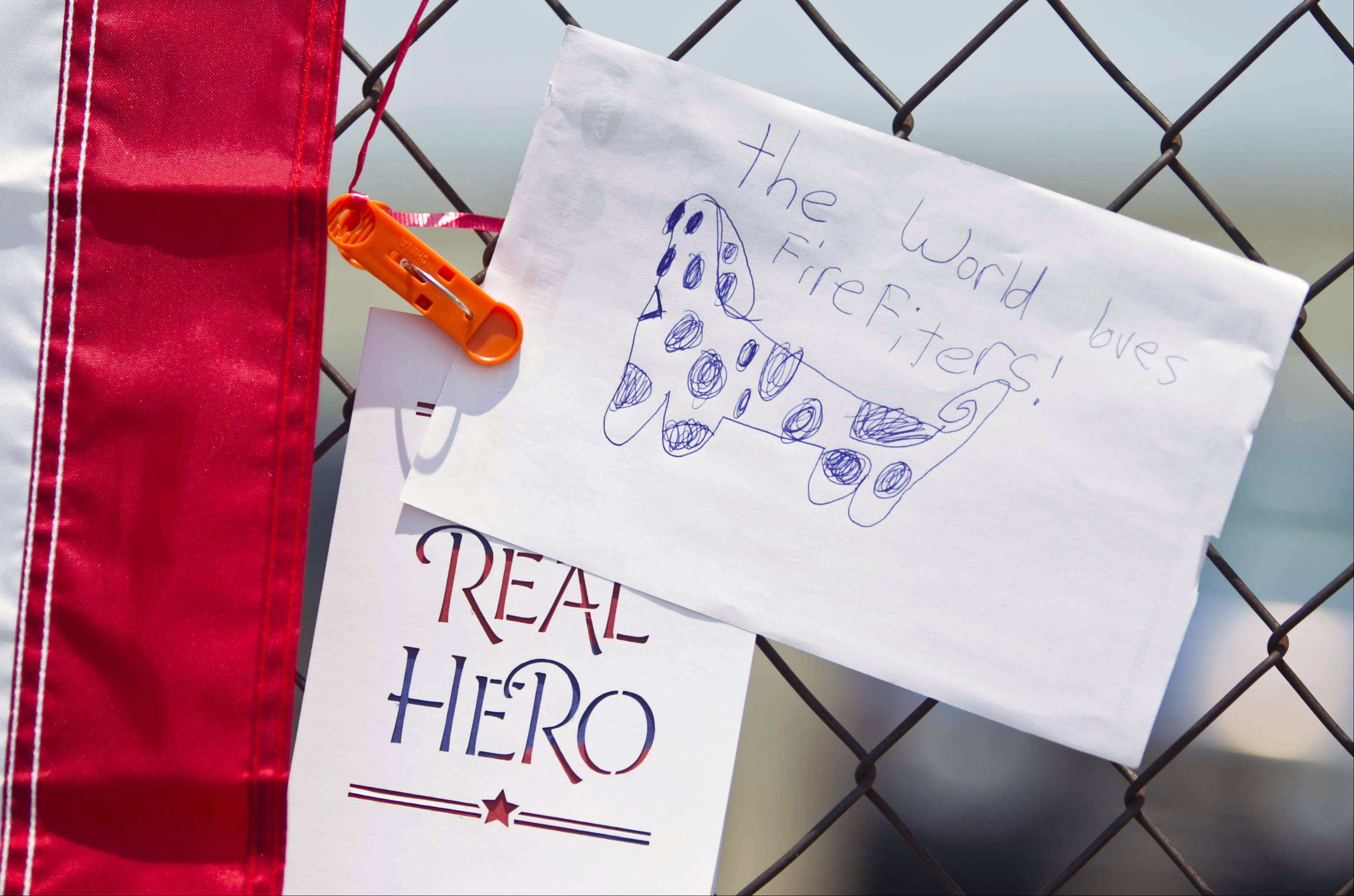 Signs are displayed at a makeshift memorial at the fire station Monday, July 1, 2013, in Prescott, Ariz.