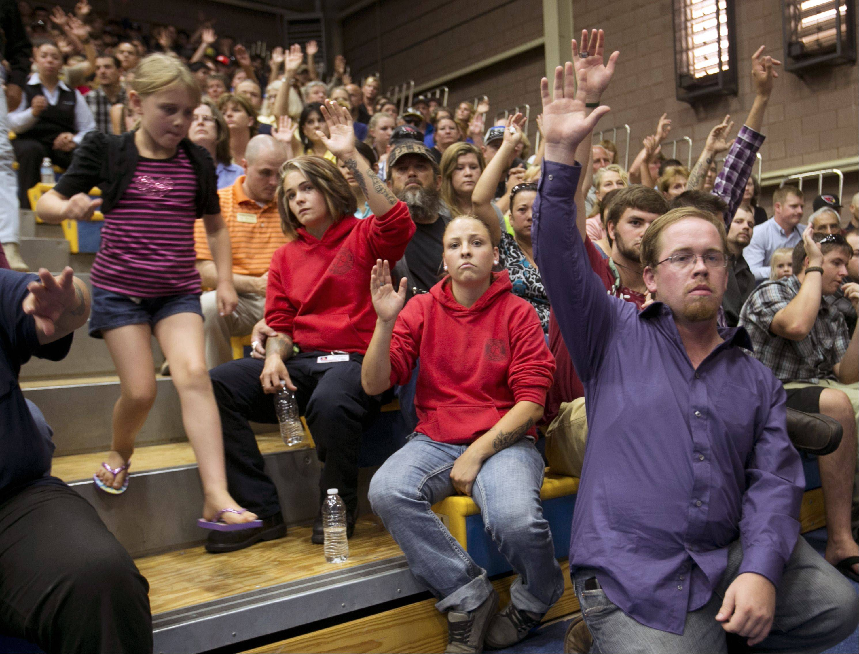 Levi Weinberger, right, raises his hand with others to indicate he knew a firefighter that was killed during a memorial service on Monday, July 1, 2013 in Prescott, Ariz.