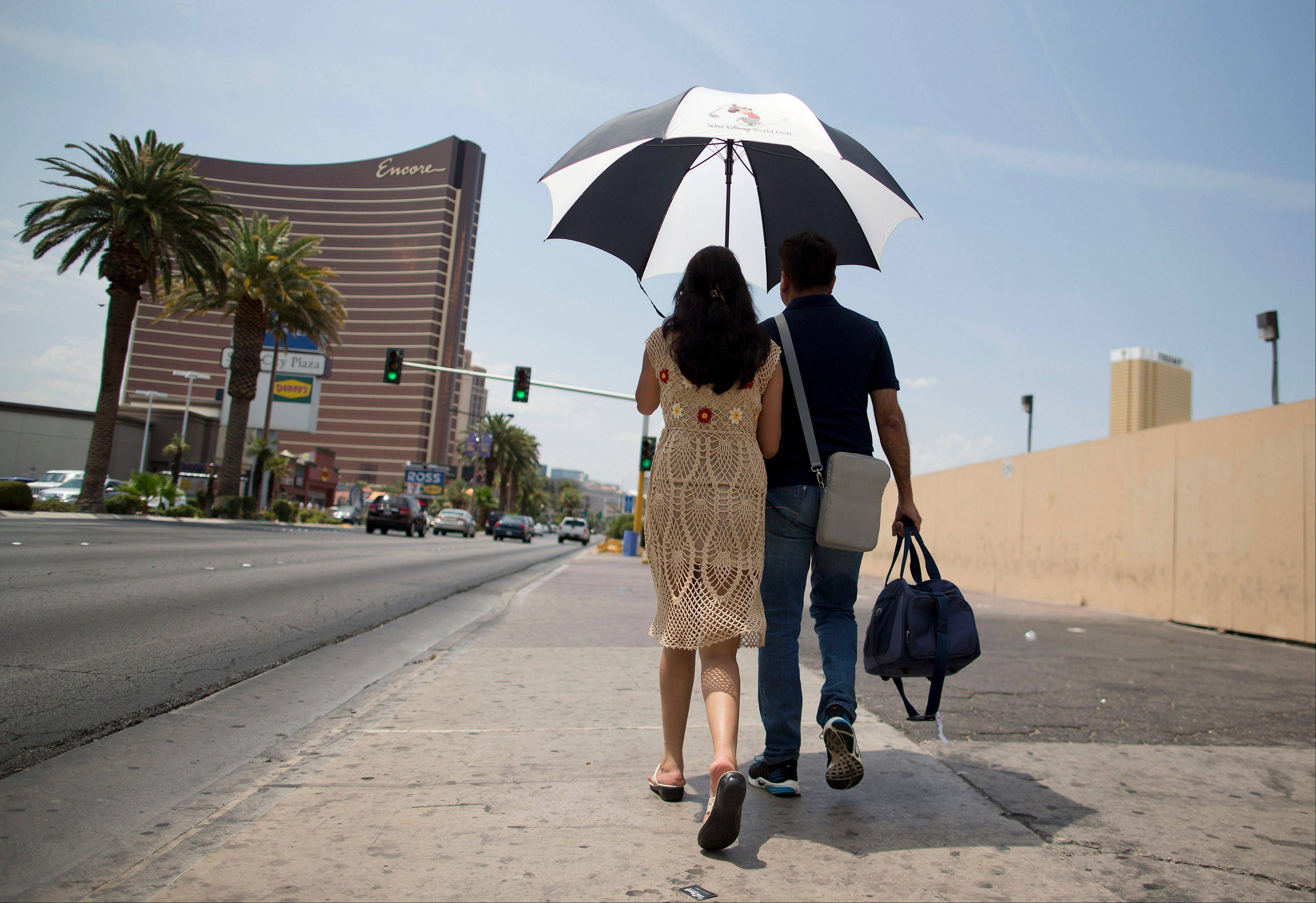 Under the shade of an umbrella with temperatures already in triple digits by mid morning, tourists walk north along Las Vegas Boulevard toward The Strip in Las Vegas. Temperatures were on the rise again after the city reported a record overnight low of 89 degrees Sunday and forecasters predicting a high of 116.