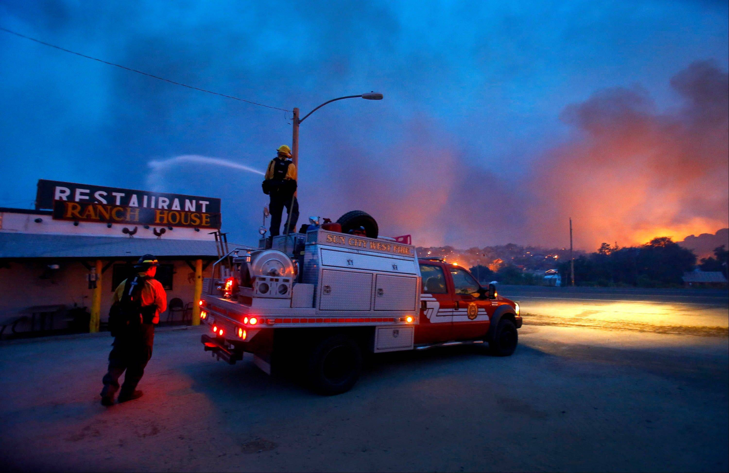 Firefighters spray water on a restaurant to help protect it from flames in the Glenn Ilah area near Yarnell, Ariz. on Sunday, June 30, 2013. An Arizona fire chief says the wildfire that killed 19 members of his crew near the town was moving fast and fueled by hot, dry conditions. The fire started with a lightning strike on Friday and spread to 2,000 acres on Sunday amid triple-digit temperatures.