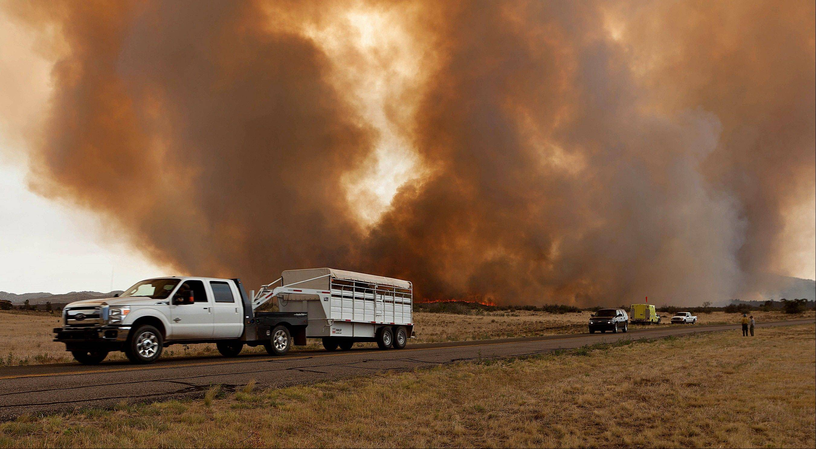 Residents evacuate along Hays Road in Peeples Valley, Ariz. as the Yarnell Hill Fire advances on Sunday, June 30, 2013. The fire started Friday and picked up momentum as the area experienced high temperatures, low humidity and windy conditions. It has forced the evacuation of residents in the Peeples Valley area and in the town of Yarnell.