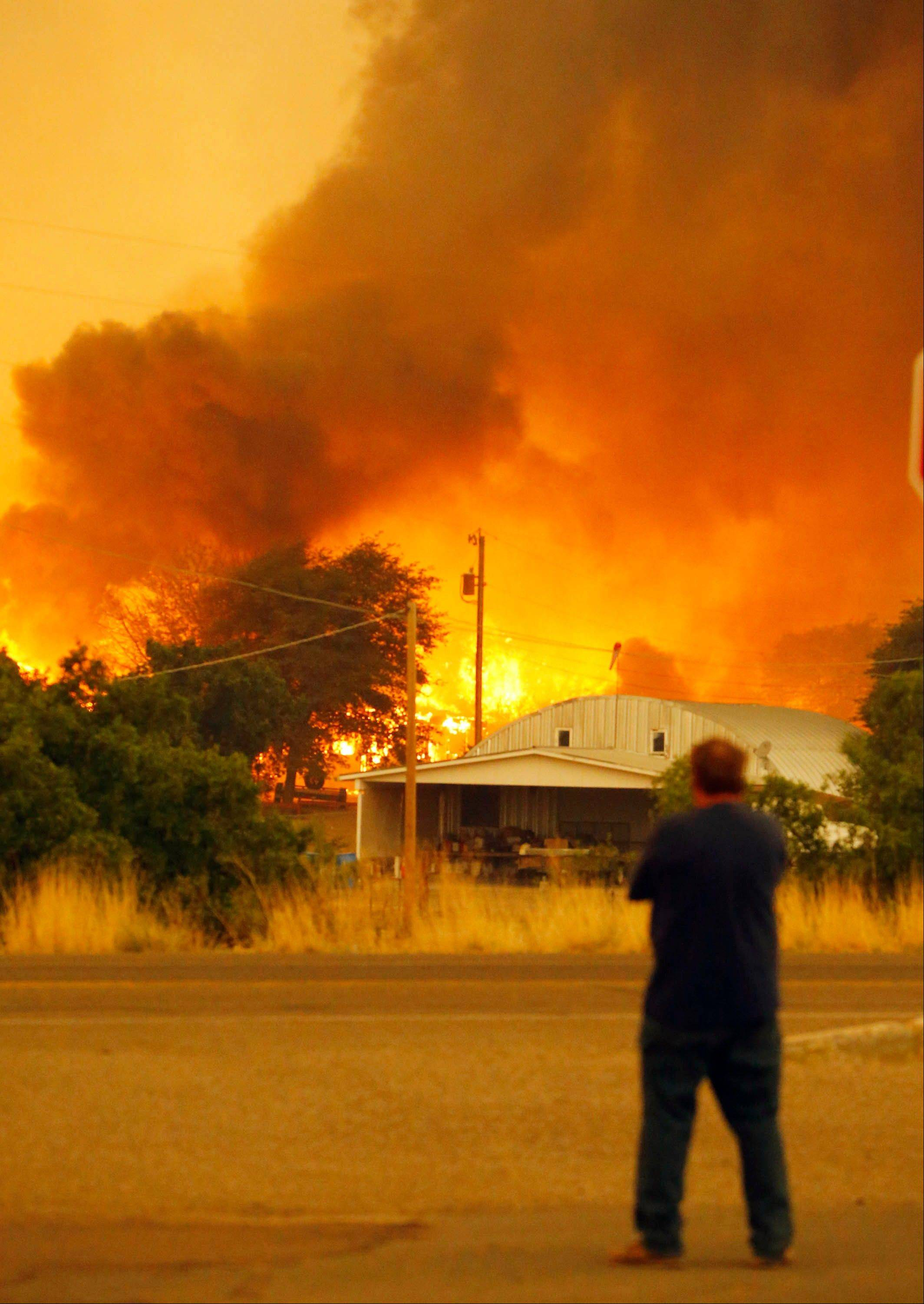 Dean Smith watches as the Yarnell Hill Fire encroaches on his home in Glenn Ilah on Sunday, June 30, 2013 near Yarnell, Ariz. The fire started Friday and picked up momentum as the area experienced high temperatures, low humidity and windy conditions. It has forced the evacuation of residents in the Peeples Valley area and in the town of Yarnell.