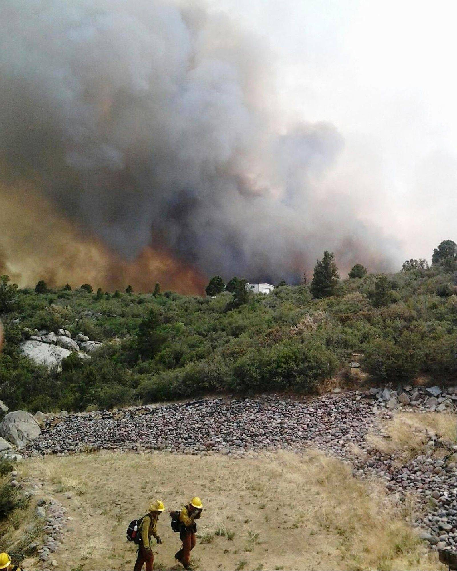 Firefighters work near a wildfire burning along a ridge in Yarnell, Ariz., in this photo provided by the U.S. Forest Service, Monday, July 1, 2013. The lightning-sparked fire, which started last Friday, spread to at least 2,000 acres amid triple-digit temperatures, overtook an elite group of firefighters, killing 19 members as they tried to protect themselves from the flames under fire-resistant shields.