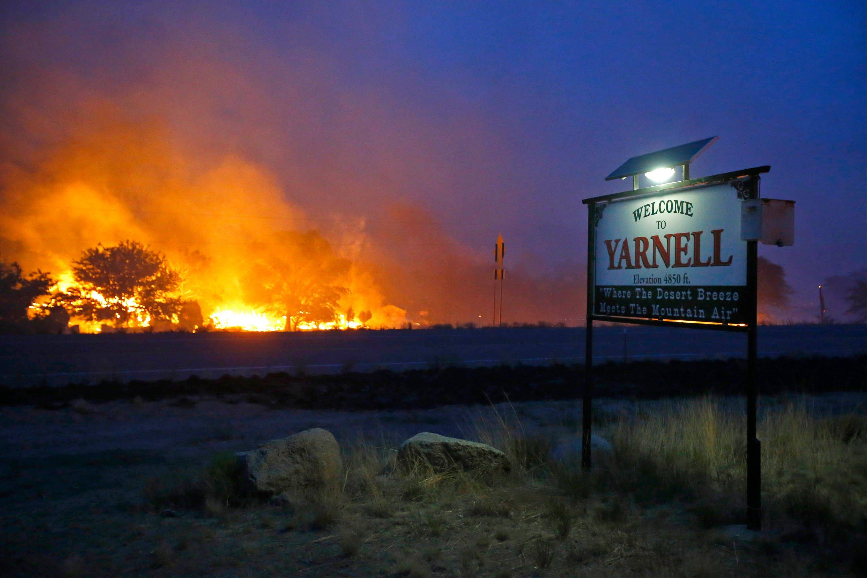 A wildfire burns homes in Yarnell, Ariz. on Sunday, June 30, 2013. An Arizona fire chief says the wildfire that killed 19 members of his crew near the town was moving fast and fueled by hot, dry conditions. The fire started with a lightning strike on Friday and spread to 2,000 acres on Sunday amid triple-digit temperatures.