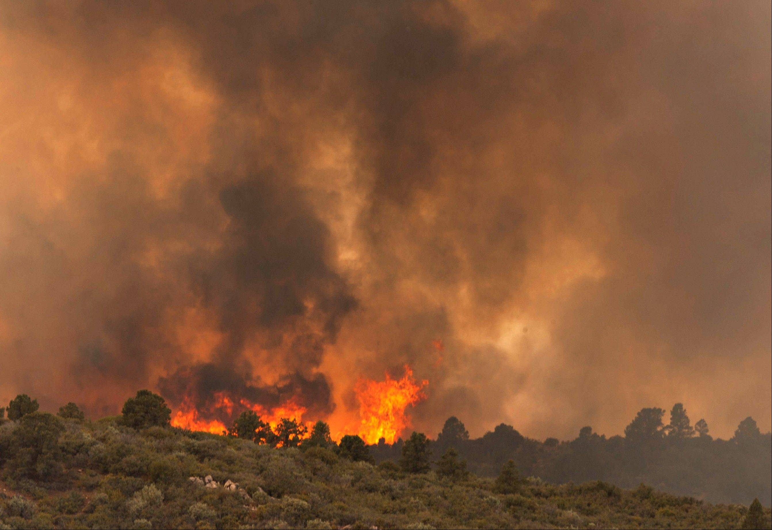 Flames top a ridge as the Yarnell Hill Fire moves toward Peeples Valley, Arizona on Sunday, June 30, 2013.