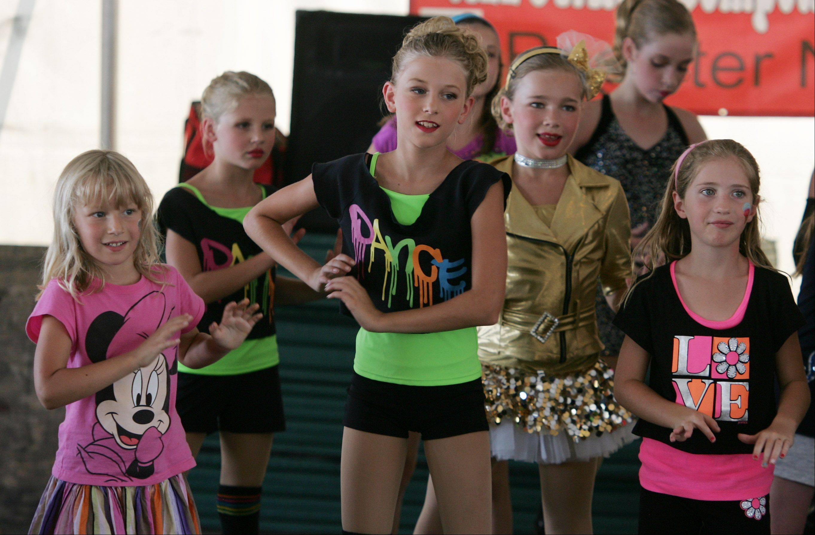Sisters Elena, left, and Grace Dallstream, center, dance with other girls from the Bataille Academie of Danse at a previous Barrington Fourth Fest.