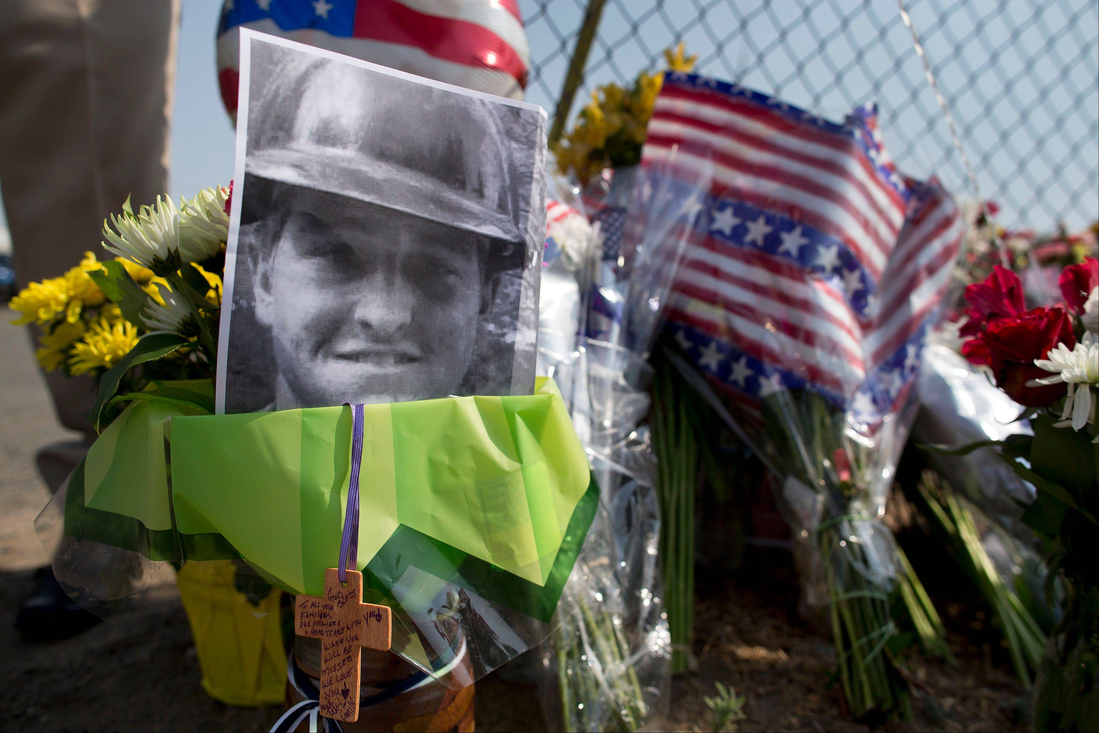 A photo of one of the 19 Granite Mountain Hot Shot crew members killed fighting a wildfire near Yarnell, Ariz., Sunday sits at a makeshift memorial outside the crew's fire station Monday in Prescott, Ariz.