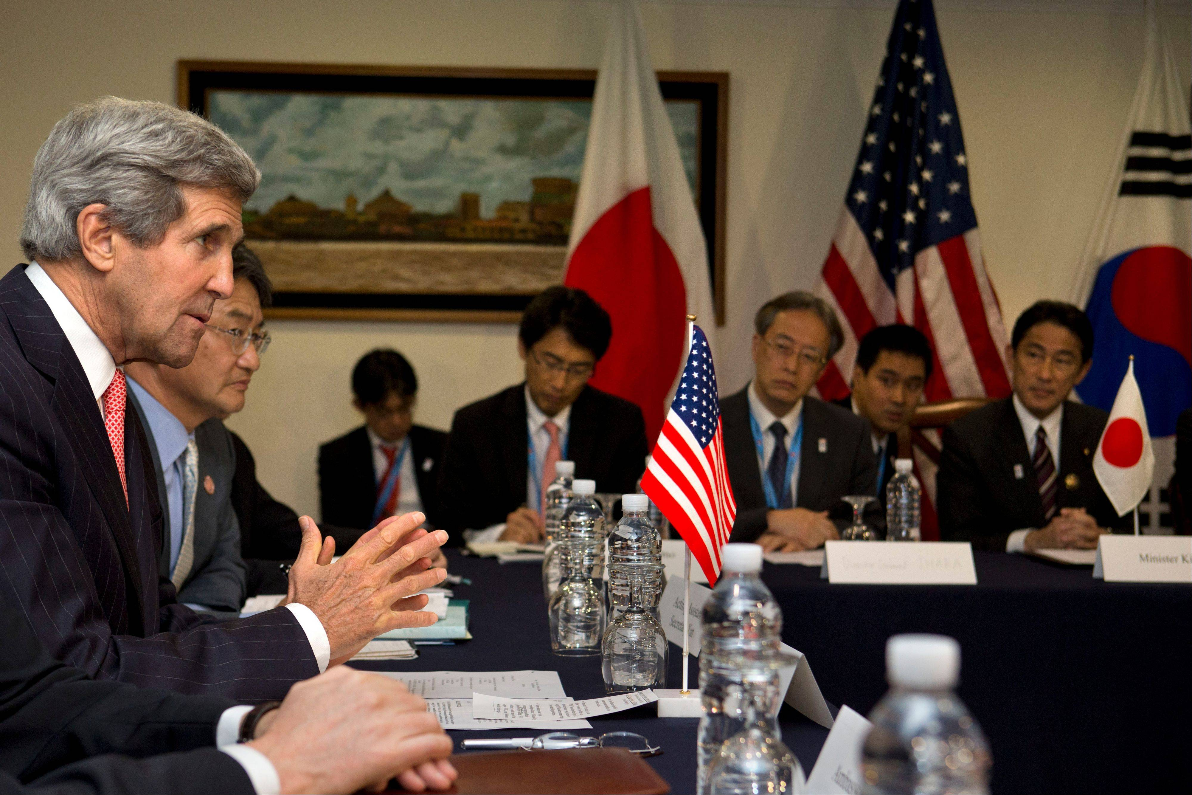 U.S. Secretary of State John Kerry, left, speaks during a meeting with Japan and South Korea during the ASEAN meetings in Bandar Seri Begawan, Brunei, on Monday.
