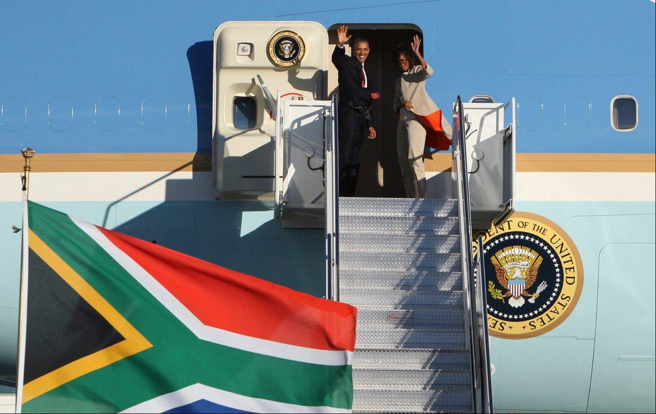U.S. President Barack Obama, left and first lady Michelle right, wave as they board their flight on Air Force One bound for Tanzania. President Obama goes to Tanzania, kicking off the final stop on his weeklong, three-country tour of sub-Saharan Africa.