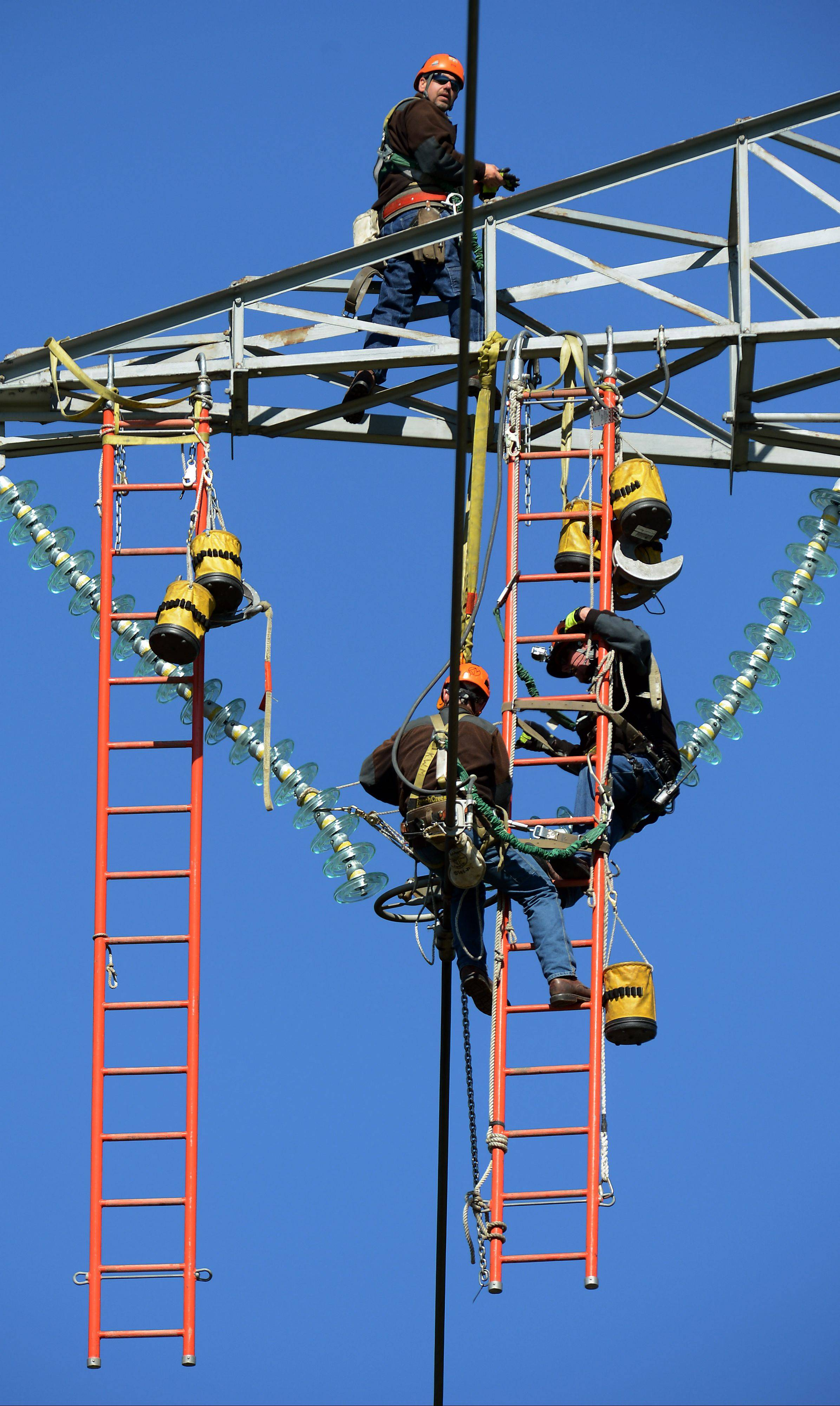 ComEd aerial specialists Ron Kellett, Ken Myers and Mike Jones work on a 130-foot electrical tower near Wayne.