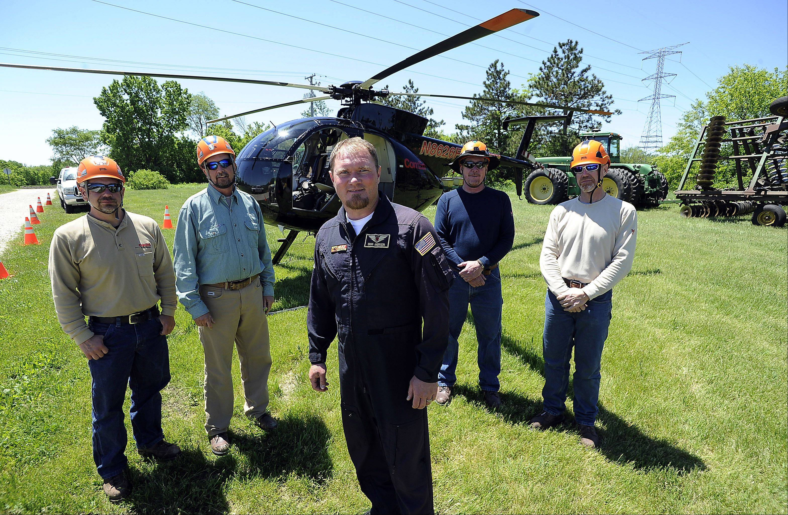 The ComEd team members of the Aerial Specialist Group are Ron Kellett of Rockford, Mike McClintock of Plainfield, Pilot Brian Anderson of Joliet, Mike Jones of Manhattan and Ken Myers of Lee get ready to fix an electrical transmission tower in Wayne.