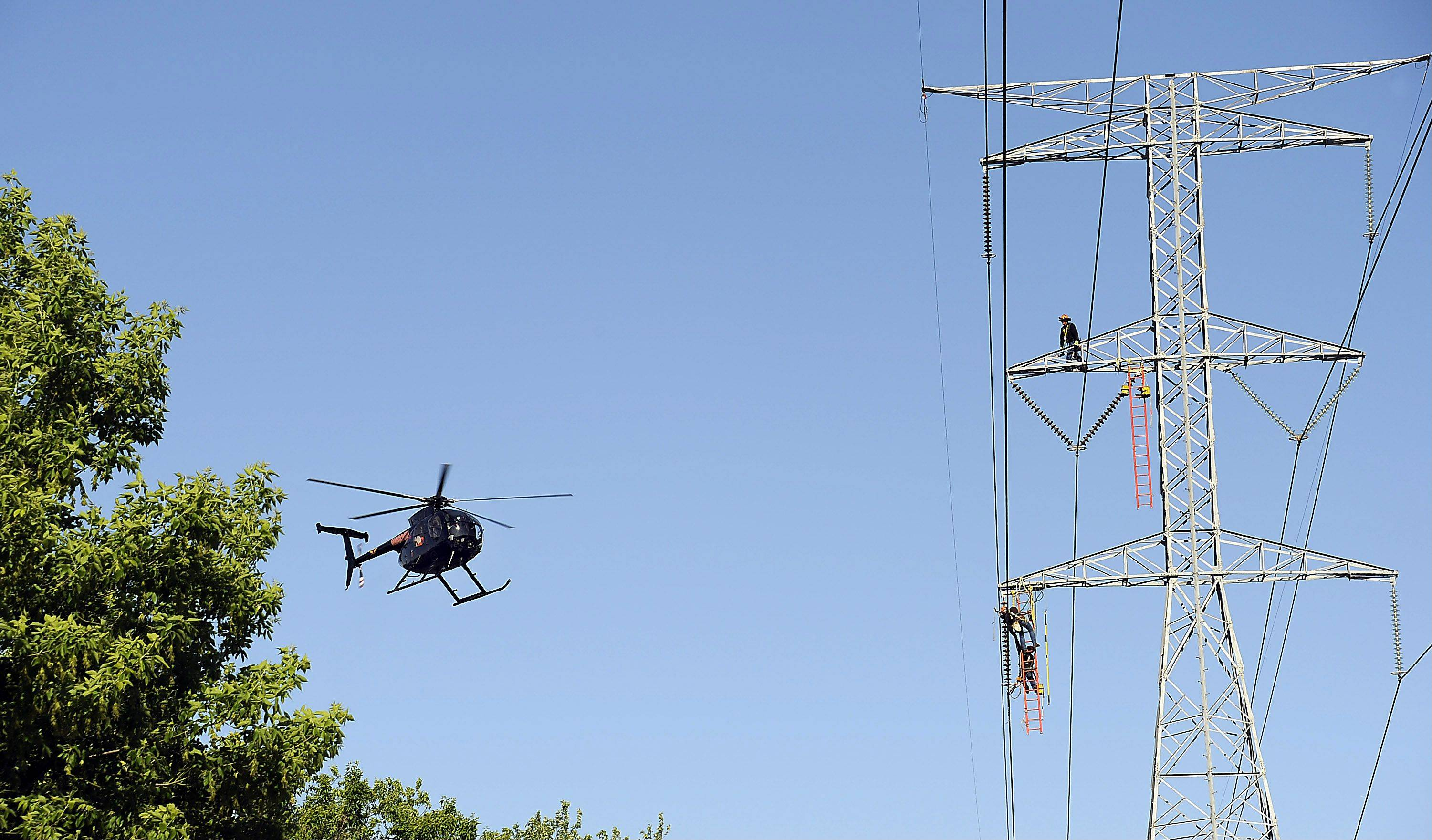 The three man team of ComEd overhead electricians on the 130ft. electrical tower position their equipment while pilot Brian Anderson hovers waiting for a hand signal to bring in the new glass insulators string to replace the porcelain ones which were made in 1964.