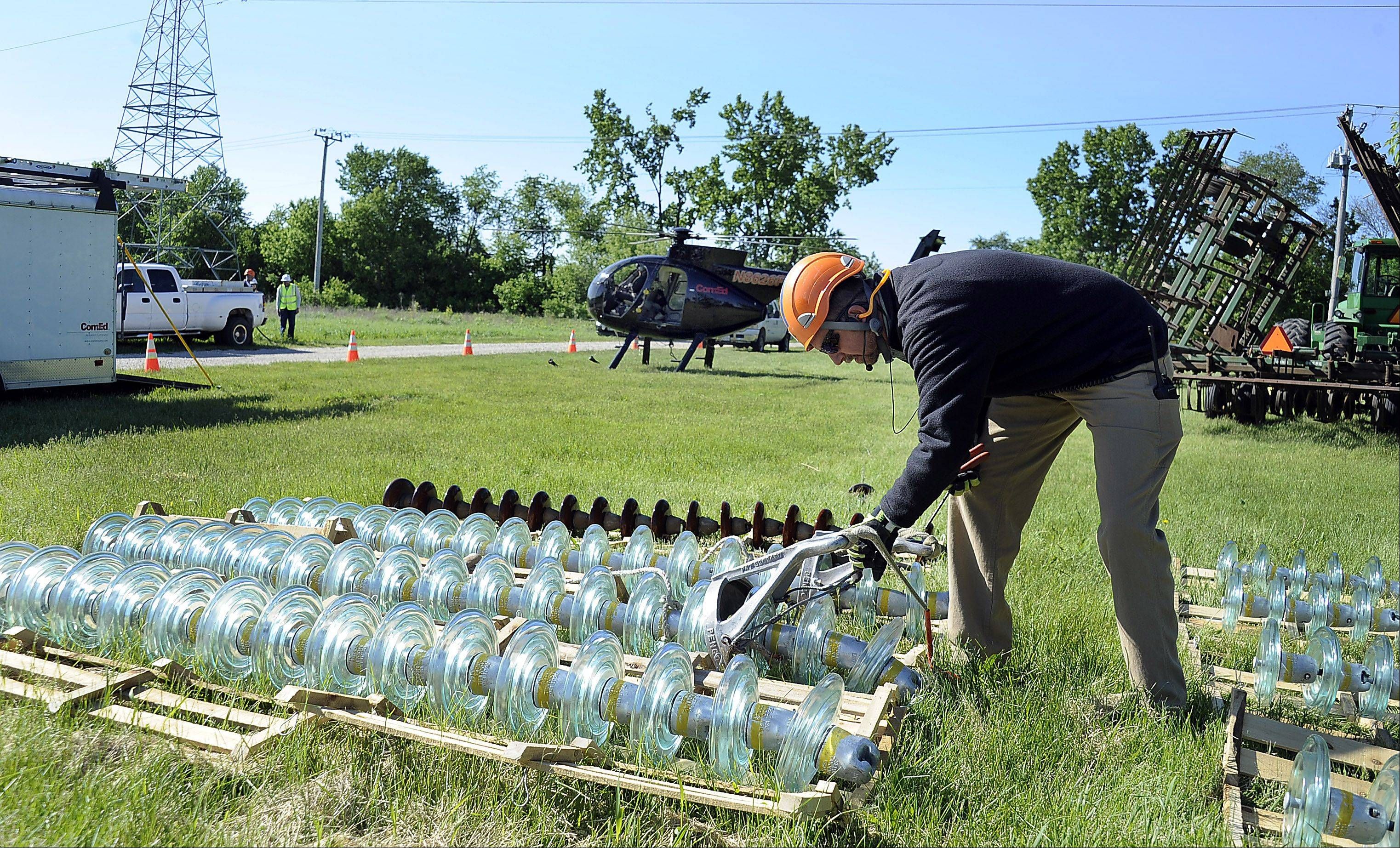 ComEd overhead electricians Mike McClintock of Plainfield hooks up a string of glass insulators which will be deliver via helicopter to the electrical tower where overhead electricians are waiting to swap them out improving service for ComEd customers.