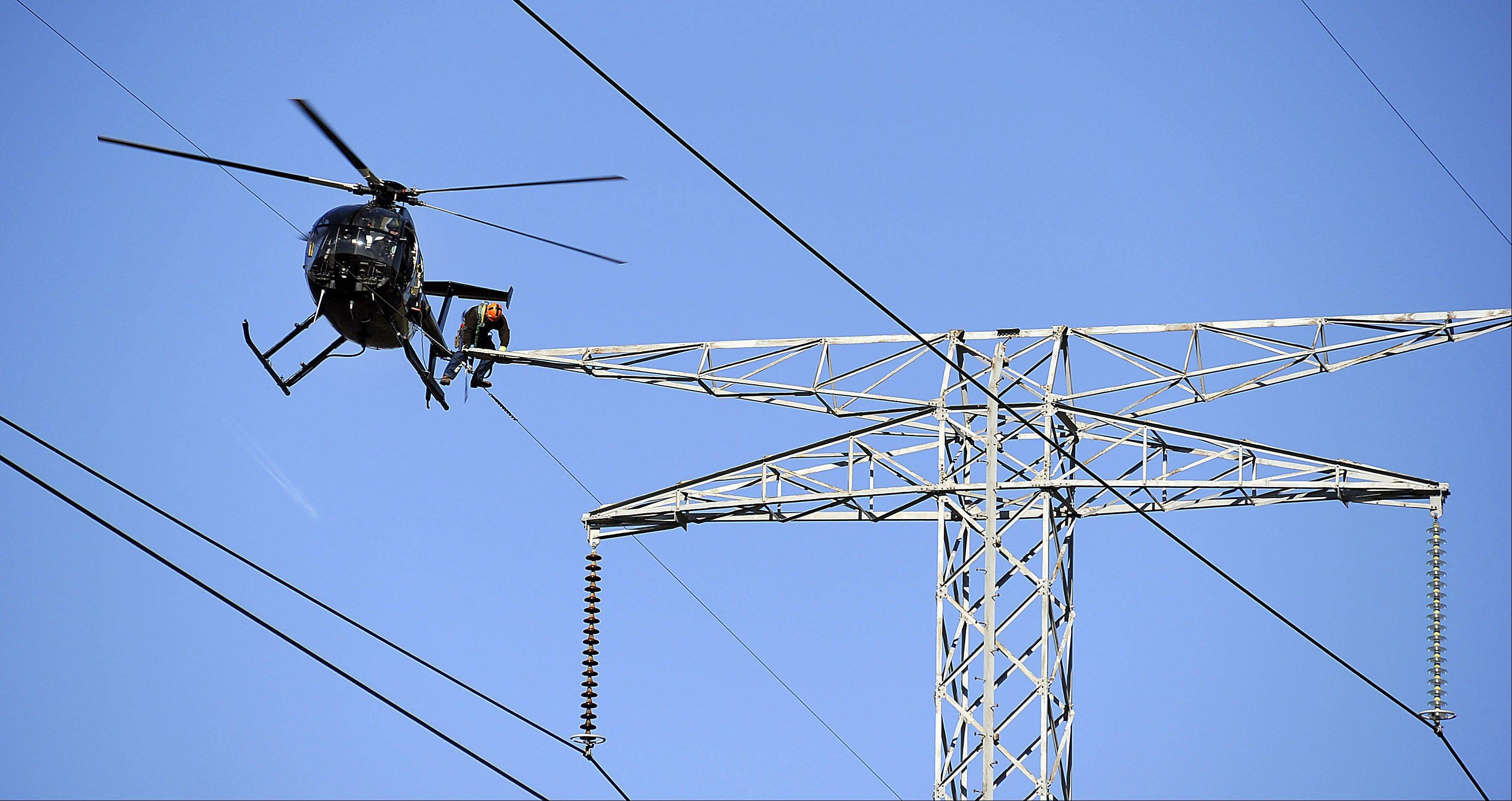 Pilot Brian Anderson positions himself inches above the 130 foot electrical tower so ComEd overhead electrician Ron Kellett can climb into the helicopter after changing porcelain insulators for new glass insulators.