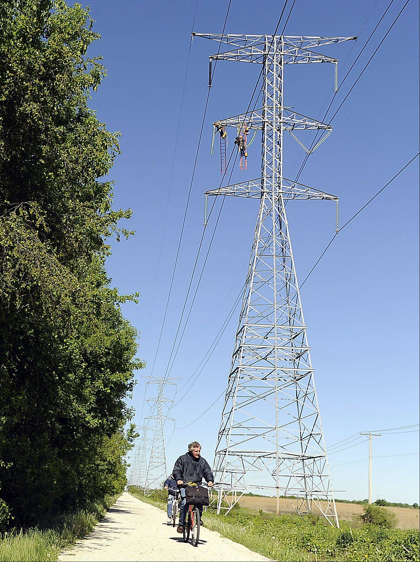 ComEd overhead electricians work on a 130 foot electrical tower above a bike path in Wayne.