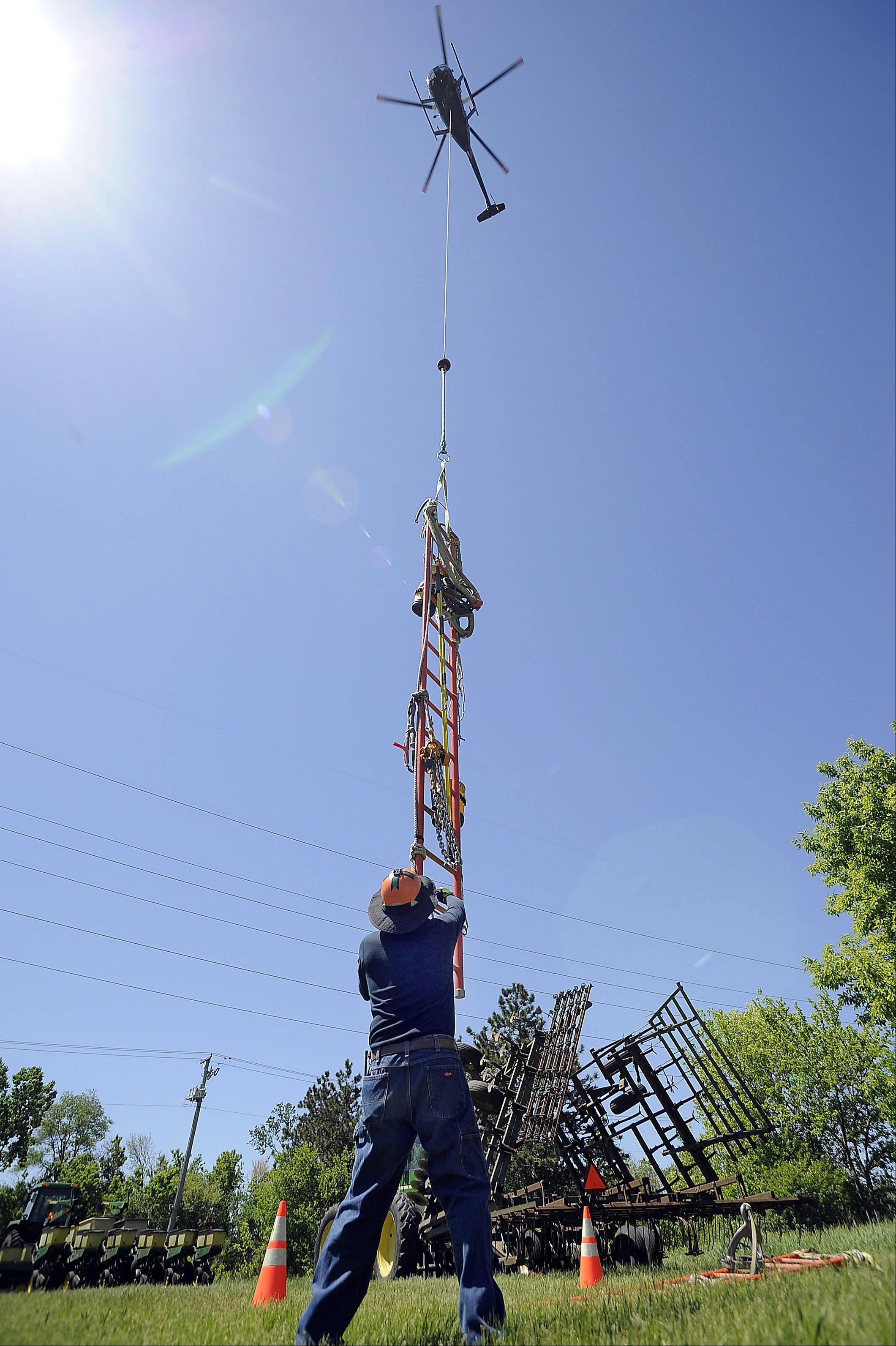 ComEd overhead electrician Mike Jones watches as ladders and other equipment are hoisted up by the helicopter to the top of the electrical tower.