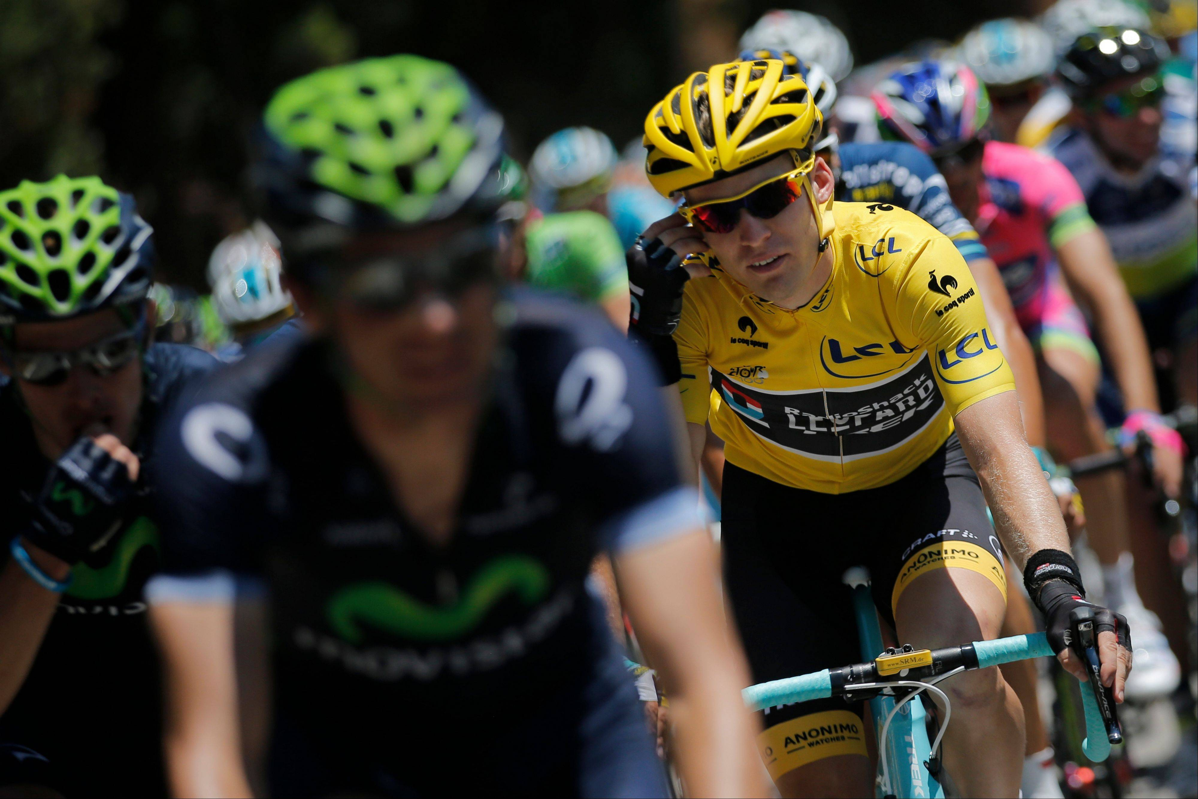 Jan Bakelants, wearing the overall leader's yellow jersey, rides in the pack Monday during the third stage of the Tour de France in Calvi, Corsica island, France.