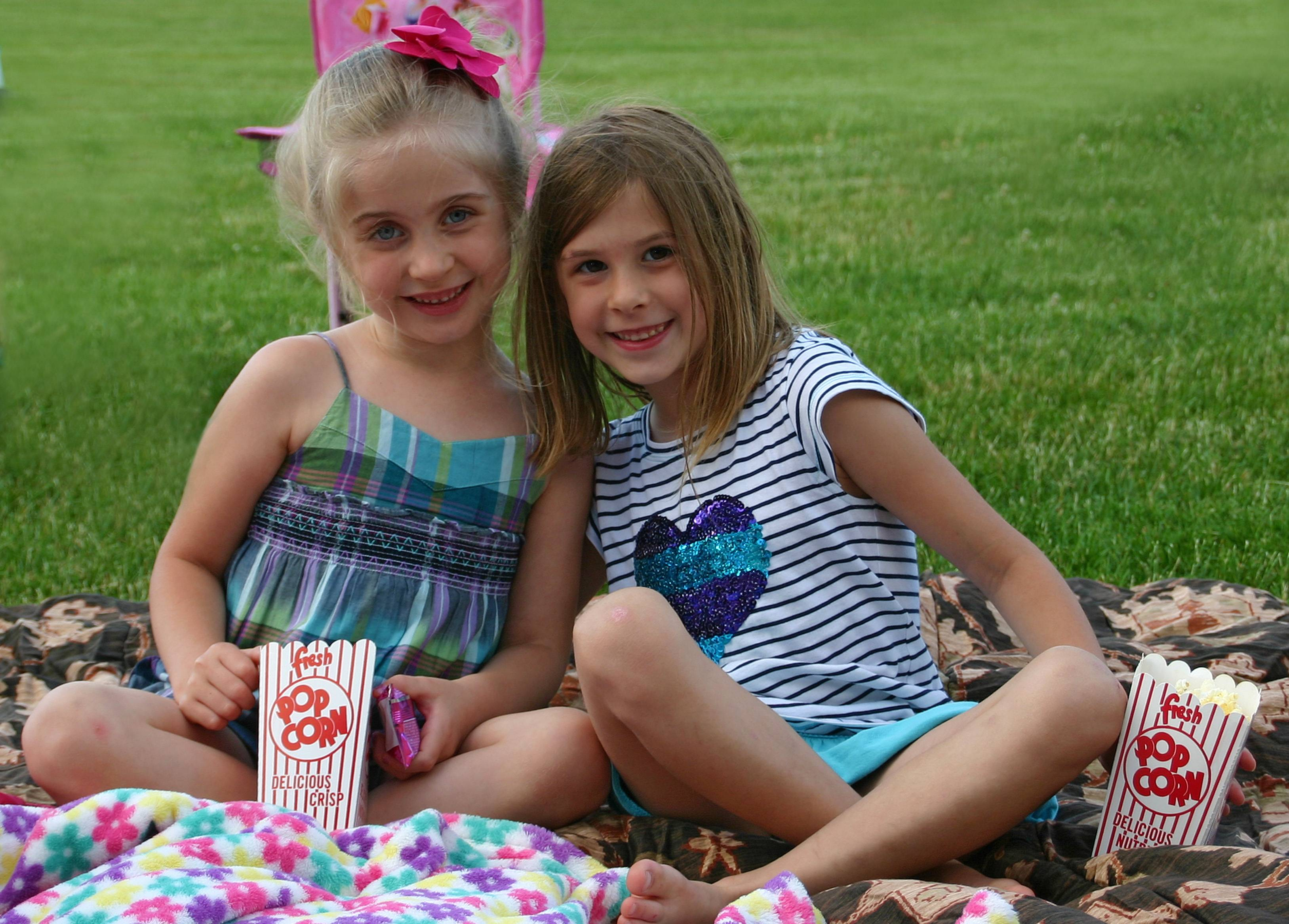 Nina Kozlik, 5-1/2, and Aubree Carl, 5, have their popcorn and are all ready for Hotel Transylvania on June 28, sponsored by the Des Plaines Optimist Club.