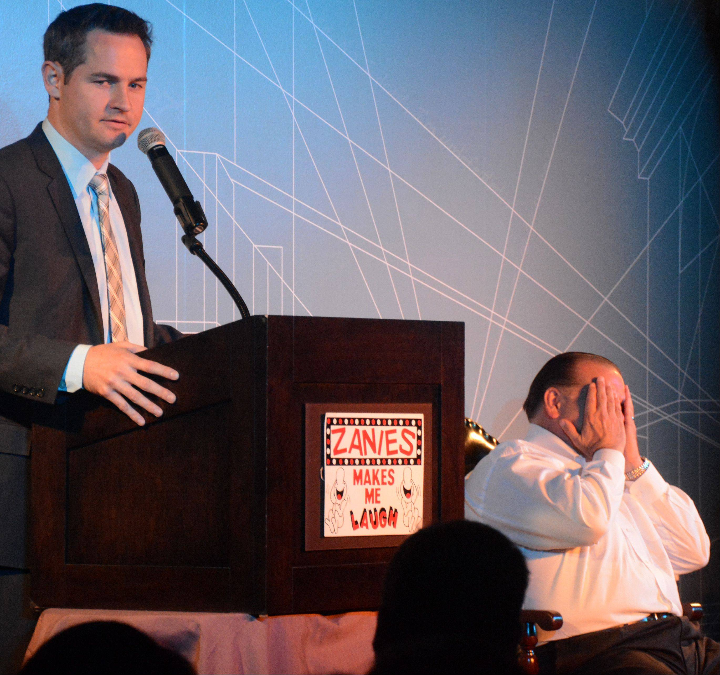 Rosemont Mayor Brad Stephens, right, covers his face as Pat McGann cracks a joke Saturday at a roast at Zanies Comedy Club in Rosemont. Proceeds from the event, which commemorates Zanies anniversary, benefit the Bear Necessities Pediatric Cancer Foundation