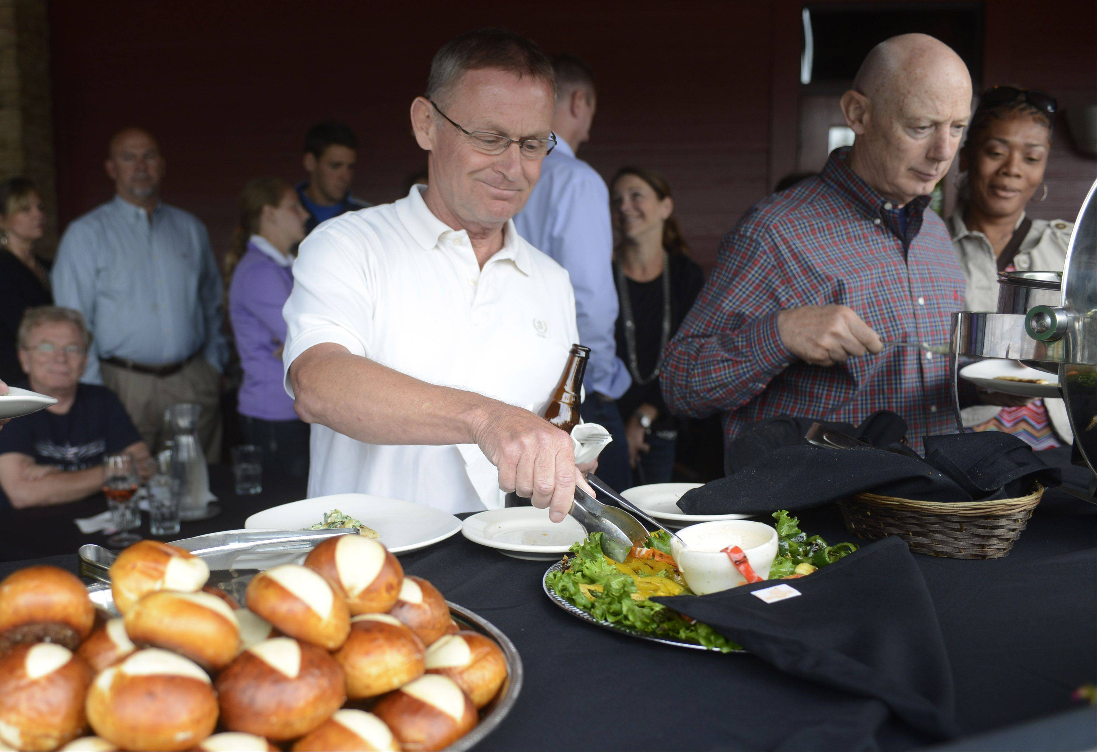 Rick Kronberg of Palatine, left, and Don Lukeon of Arlington Heights make their selections in the buffet line as Daily Herald premium subscribers are treated to �Grilling University,� a two-hour tutorial accompanied by food and drinks at Weber Grill Restaurant in Schaumburg Tuesday.