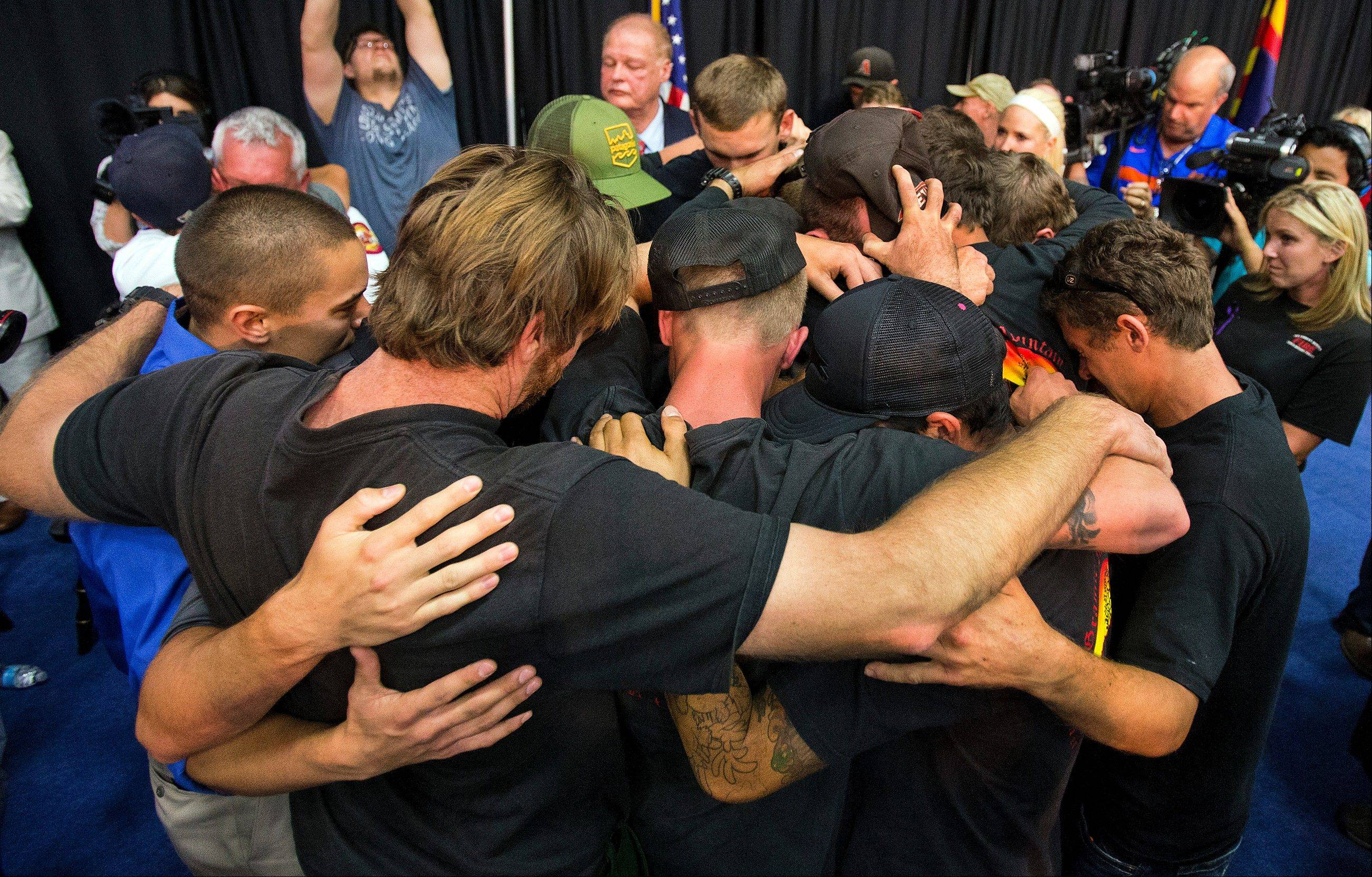 Firefighters gather in an embrace to a standing ovation during a memorial service for 19 firefighters of the Granite Mountain Hotshot Crew that were killed battling a wildfire.