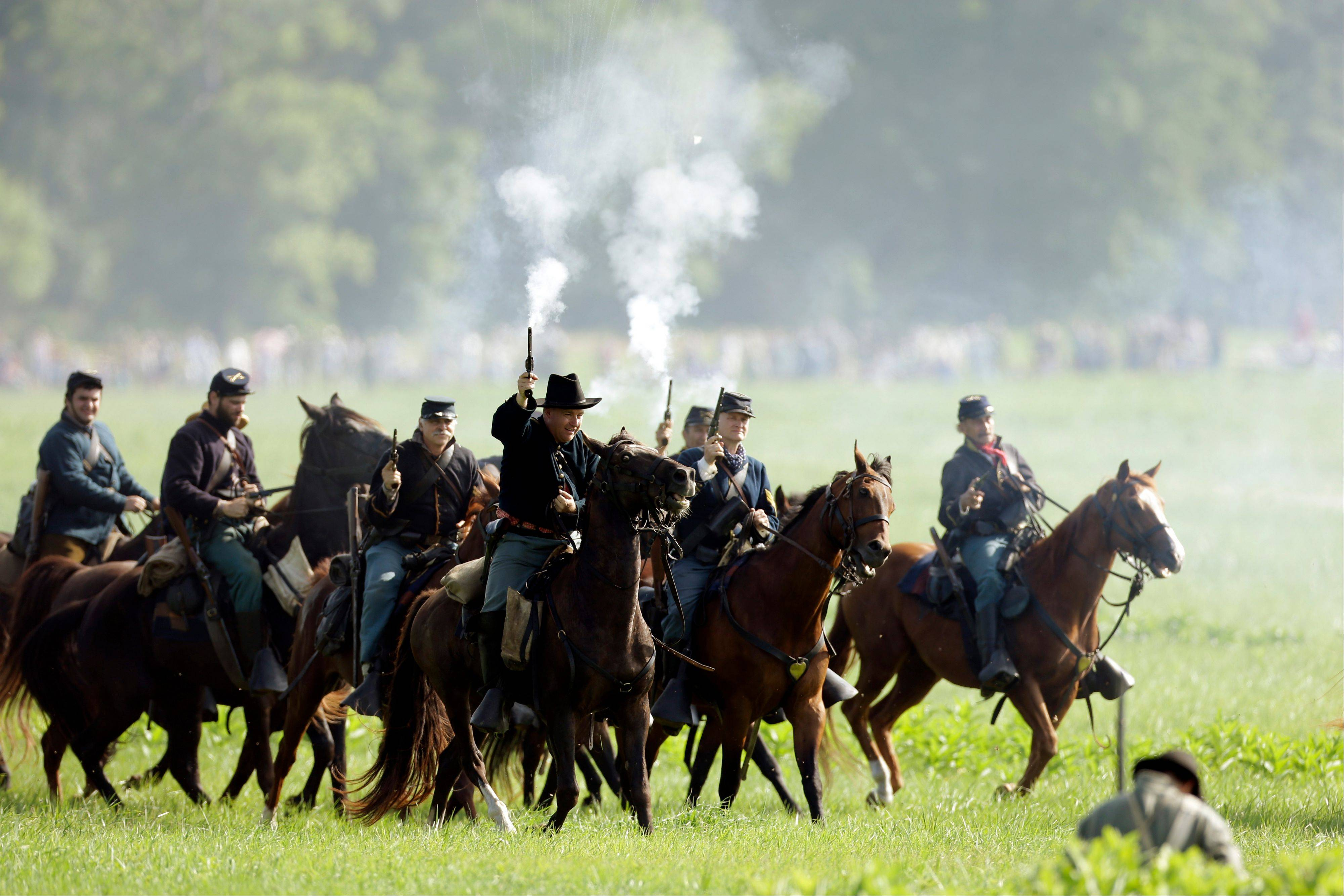 Mounted Union reenactors takes part in a demonstration of a battle during ongoing activities commemorating the 150th anniversary of the Battle of Gettysburg.