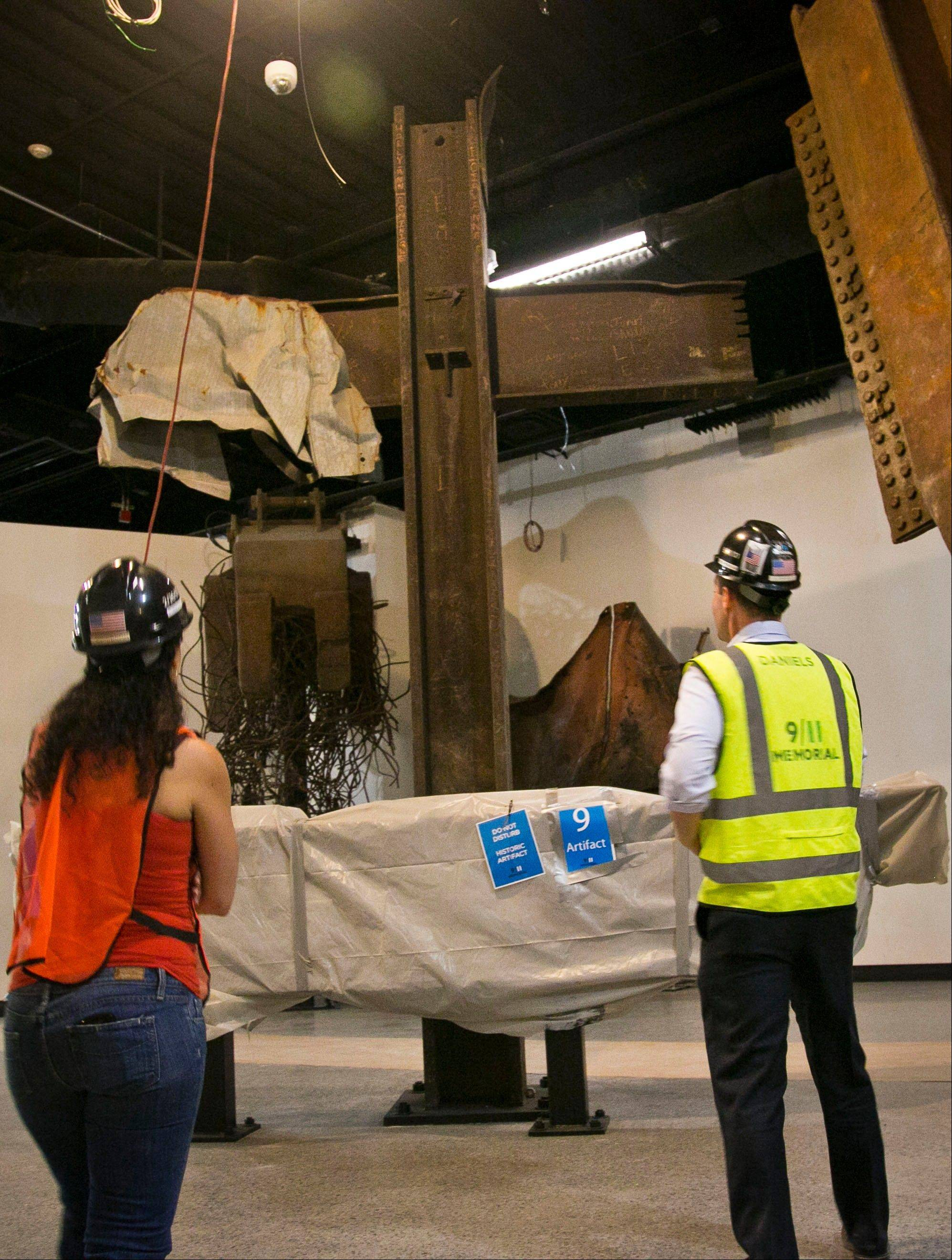 Joe Daniels, right, 911 Memorial president, and Anthoula Katsimatides, left, a member of the 911 Memorial board, approach a steel cross beam recovered from the World Trade Center (WTC) site and installed at the 911 Memorial Museum.