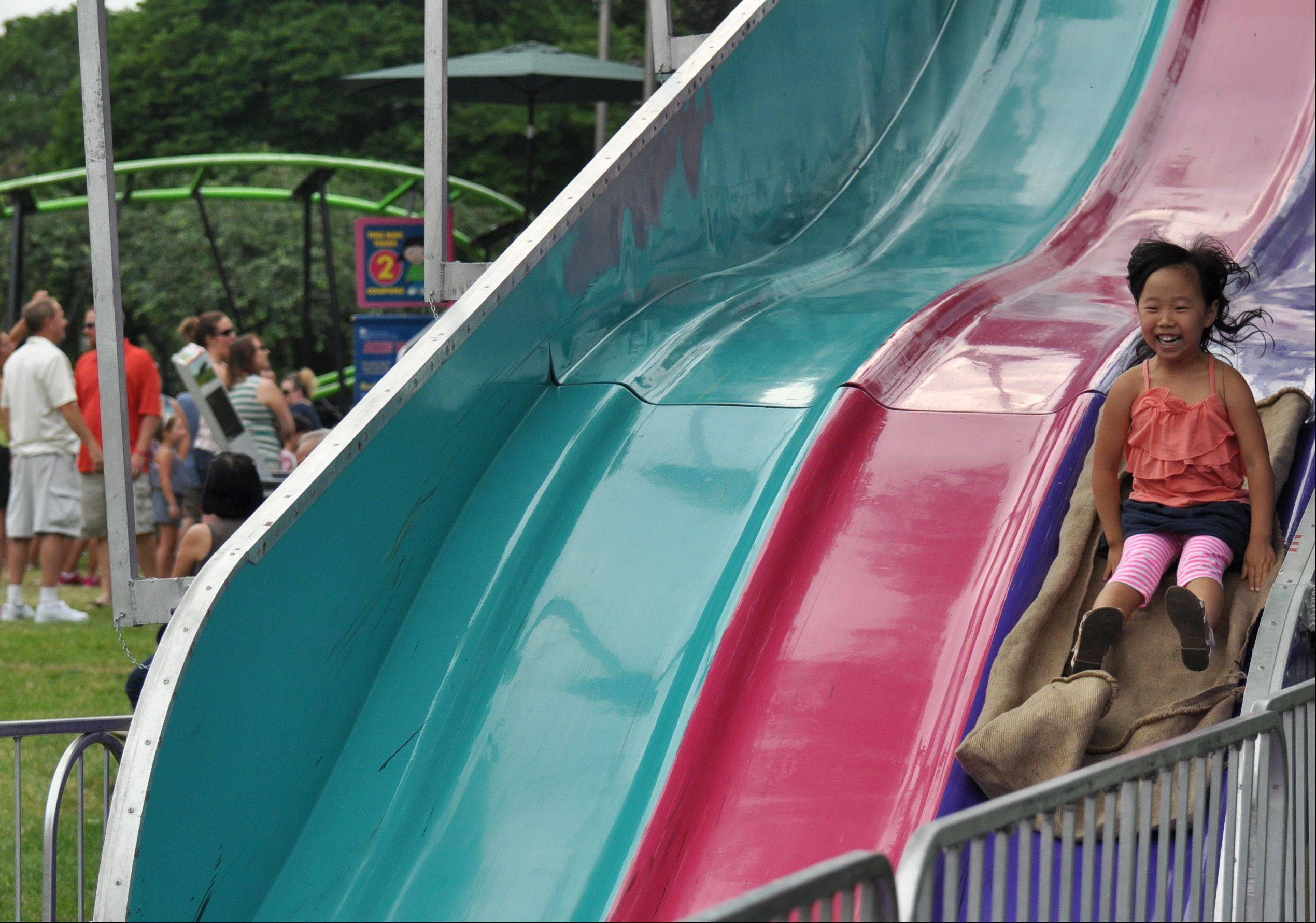 Kara Kim, 5, of Arlington Heights, rides the fun slide at Frontier Days in Arlington Heights on Saturday.
