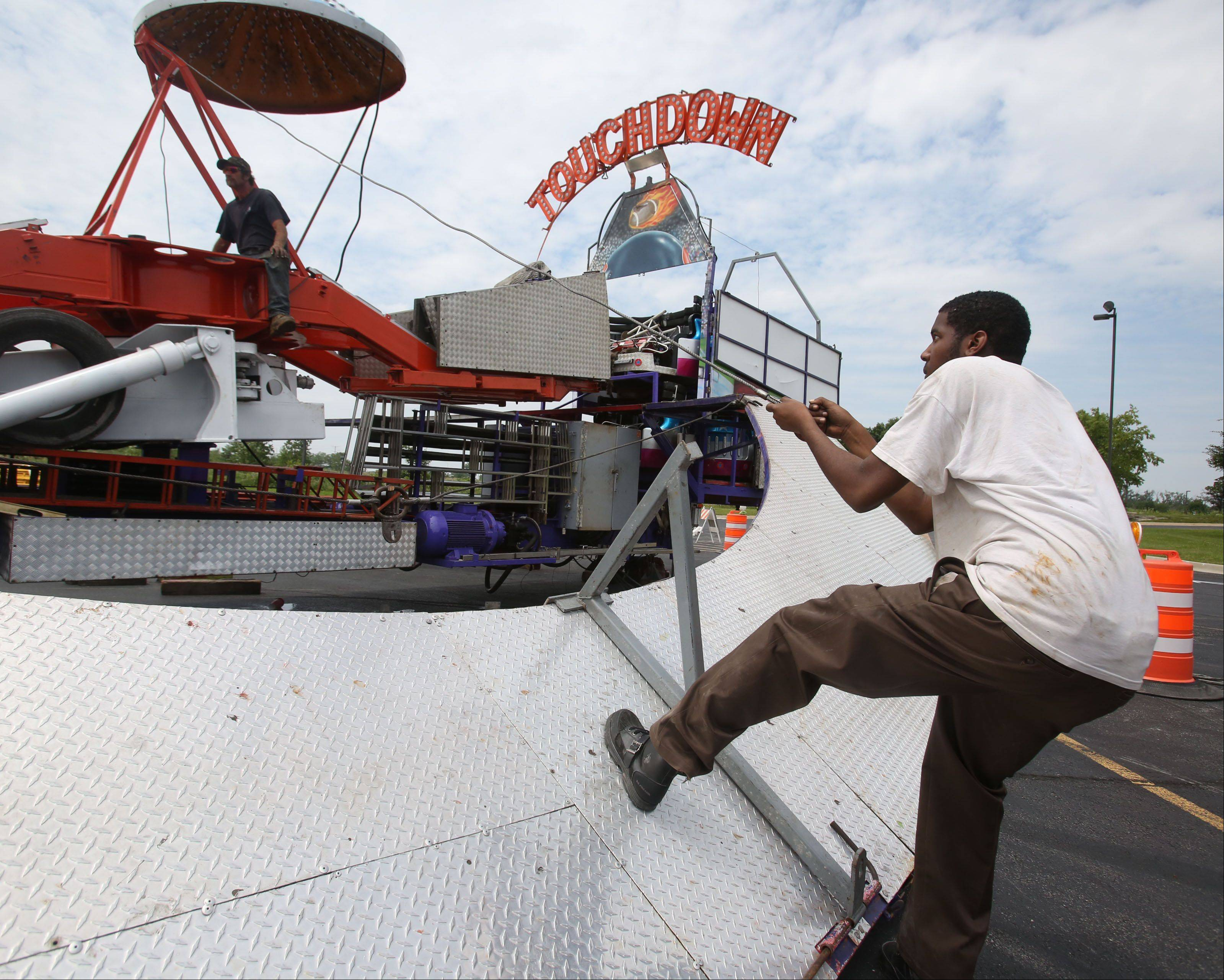 Paul Smiley of Chicago pulls on a cable as he and other workers set up the Touchdown ride in the Sears Centre parking lot.