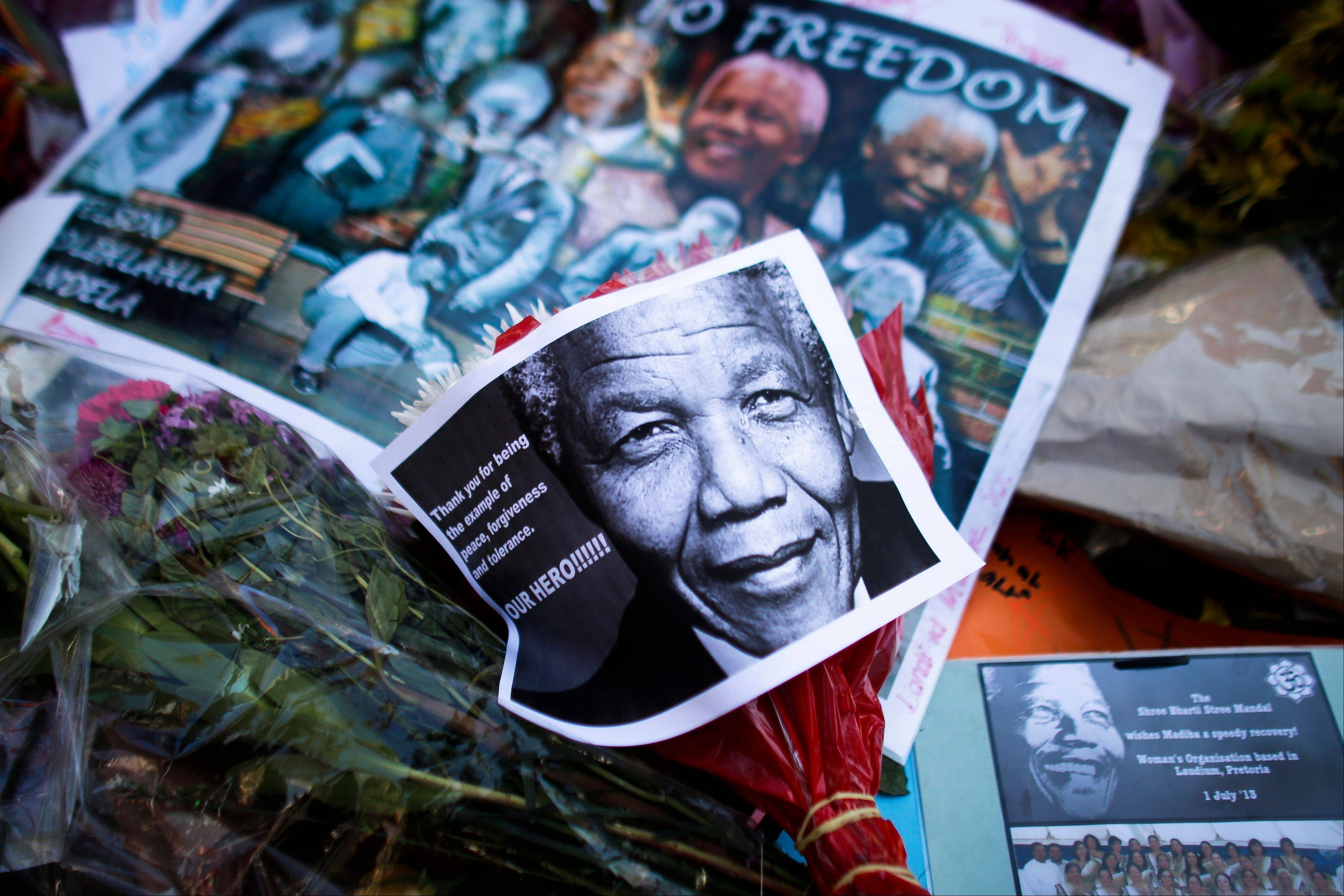 Photos, flowers and good wishes laid in support of former South African President Nelson Mandela, at the entrance of the Mediclinic Heart Hospital where Nelson Mandela is being treated in Pretoria, South Africa, Tuesday, July 2, 2013. Mandela remained in a critical condition on Tuesday.