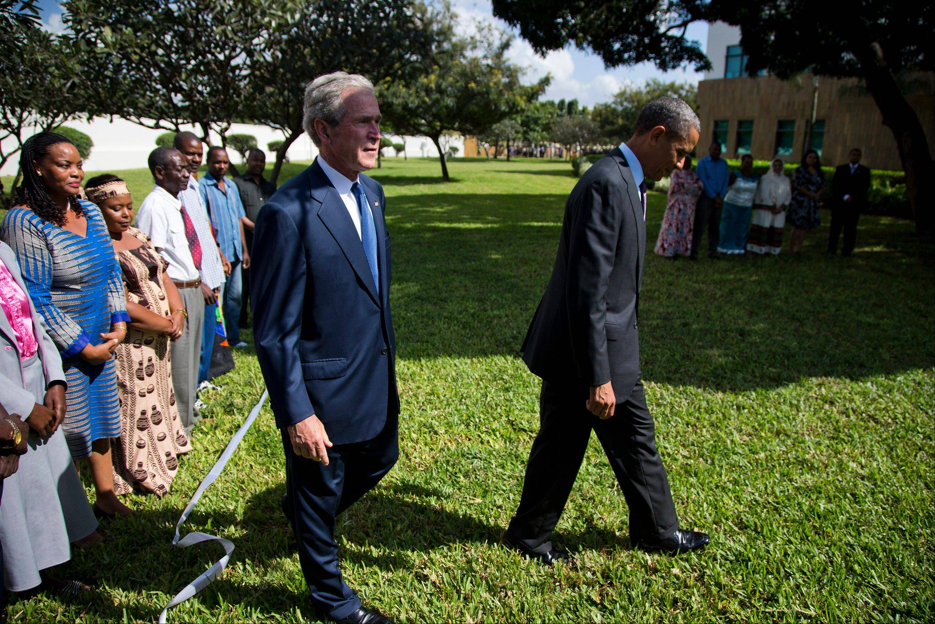U.S. President Barack Obama, right, and former President George W. Bush walk off after a wreath-laying ceremony to honor the victims of the U.S. embassy bombing on Tuesday, July 2, 2013, in Dar Es Salaam, Tanzania. The president is traveling in Tanzania on the final leg of his three-country tour in Africa.